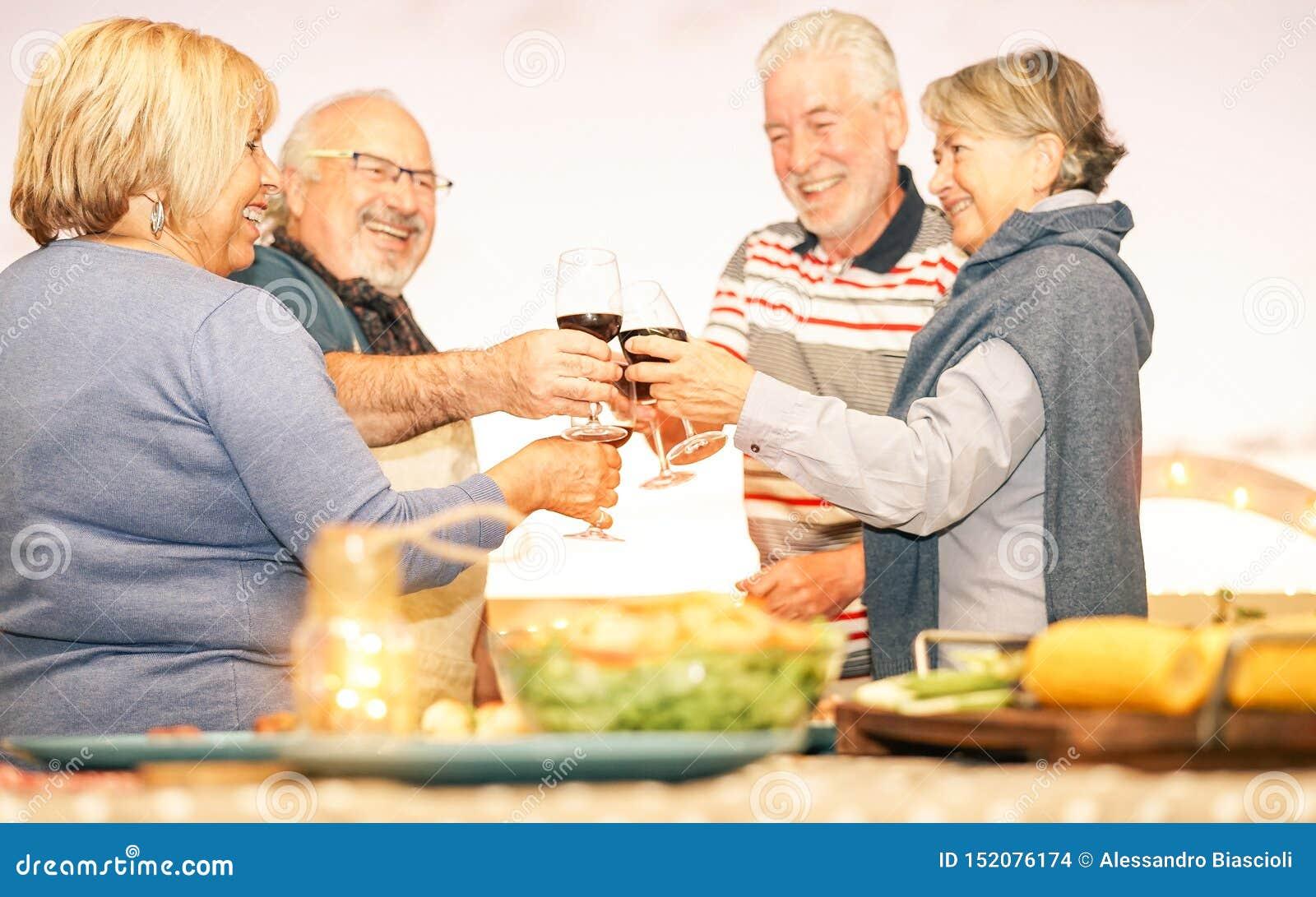 Amigos mayores felices que tuestan con el vino tinto en la cena de la barbacoa en terraza - gente madura que cena y que anima jun