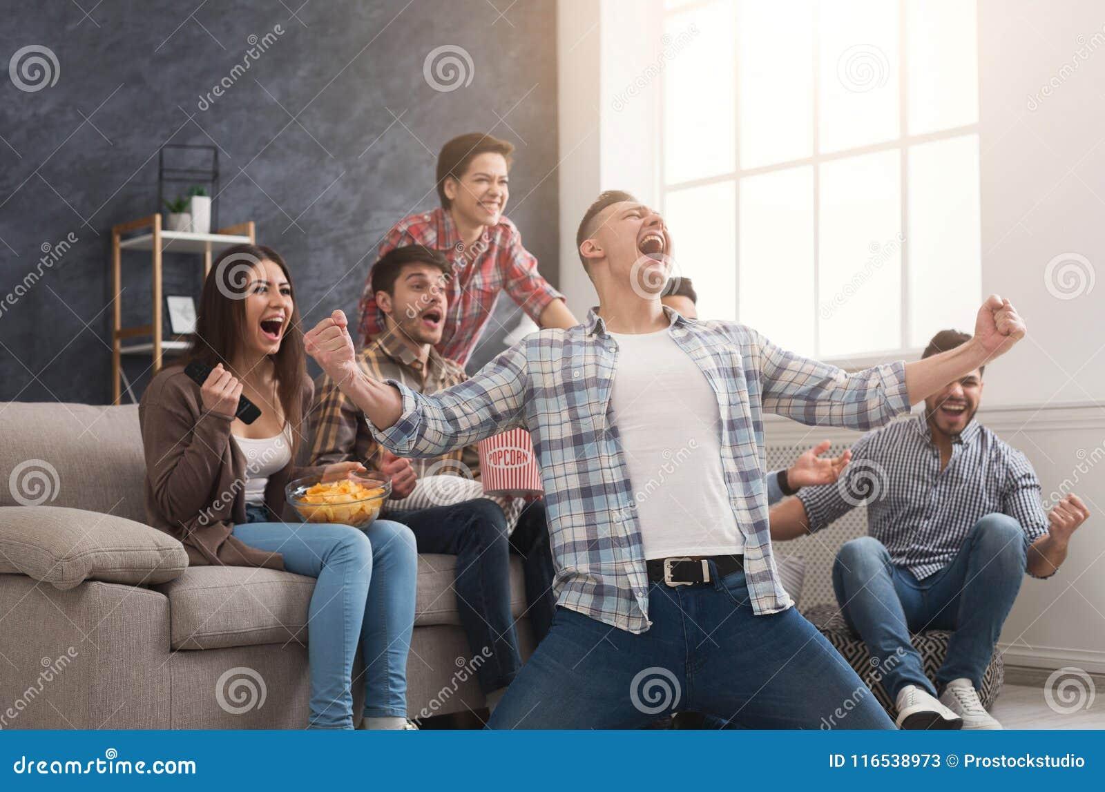 Amigos muito entusiasmado que olham o fósforo de futebol em casa