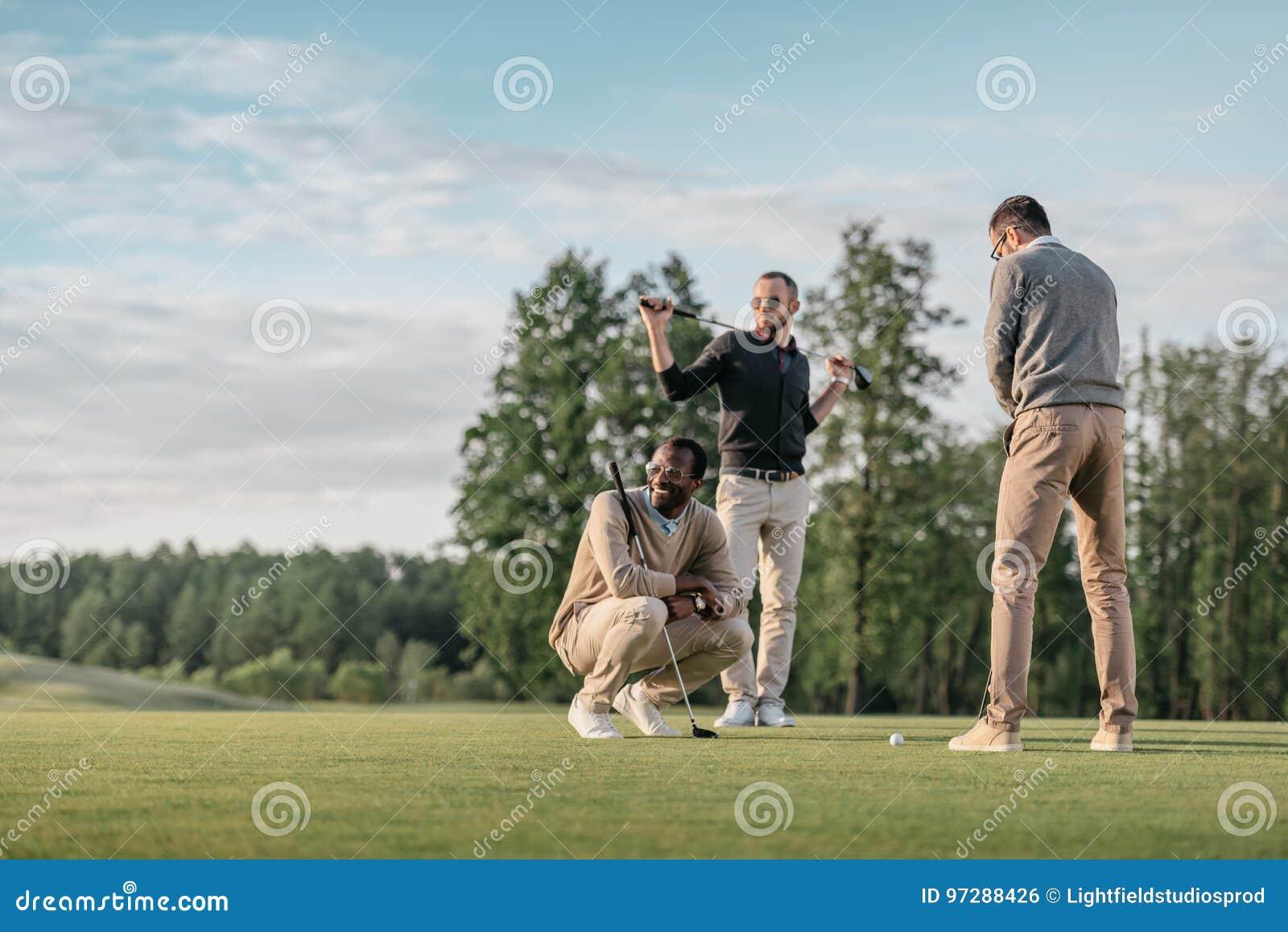Amigos multiculturales que pasan el tiempo junto mientras que juega a golf en campo de golf
