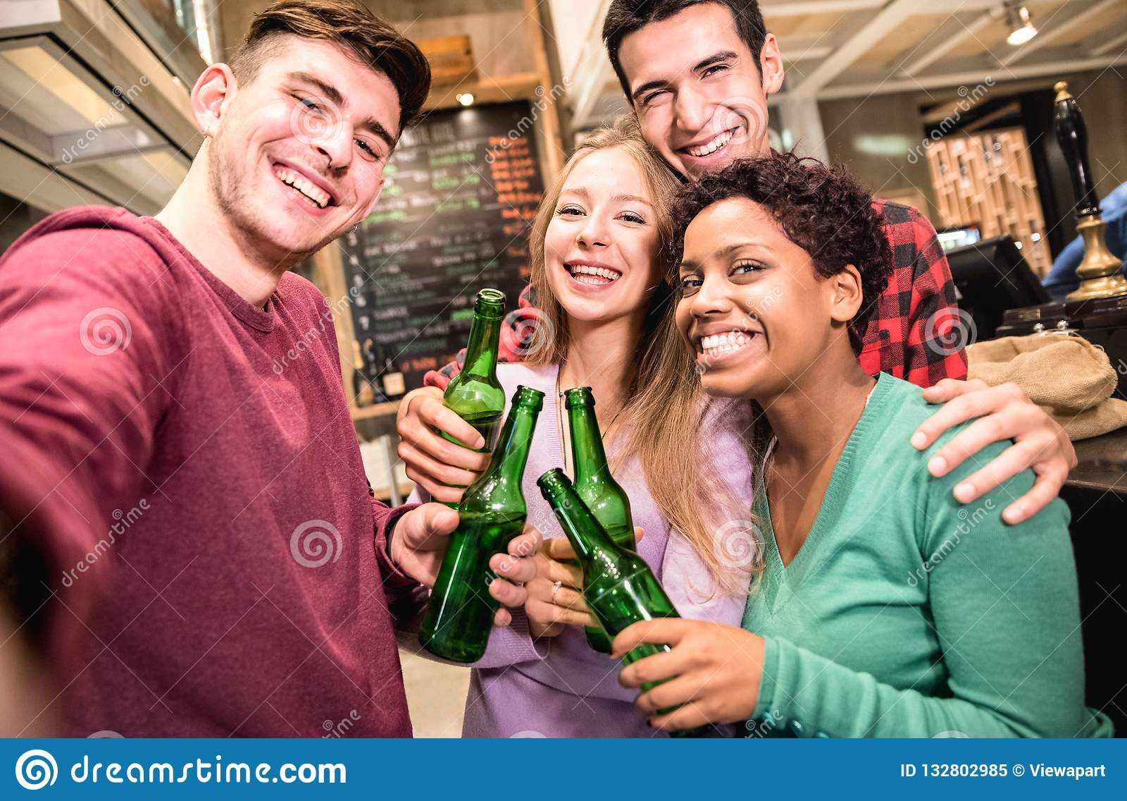 Amigos multirraciais que tomam o selfie e que bebem a cerveja no bar extravagante da cervejaria