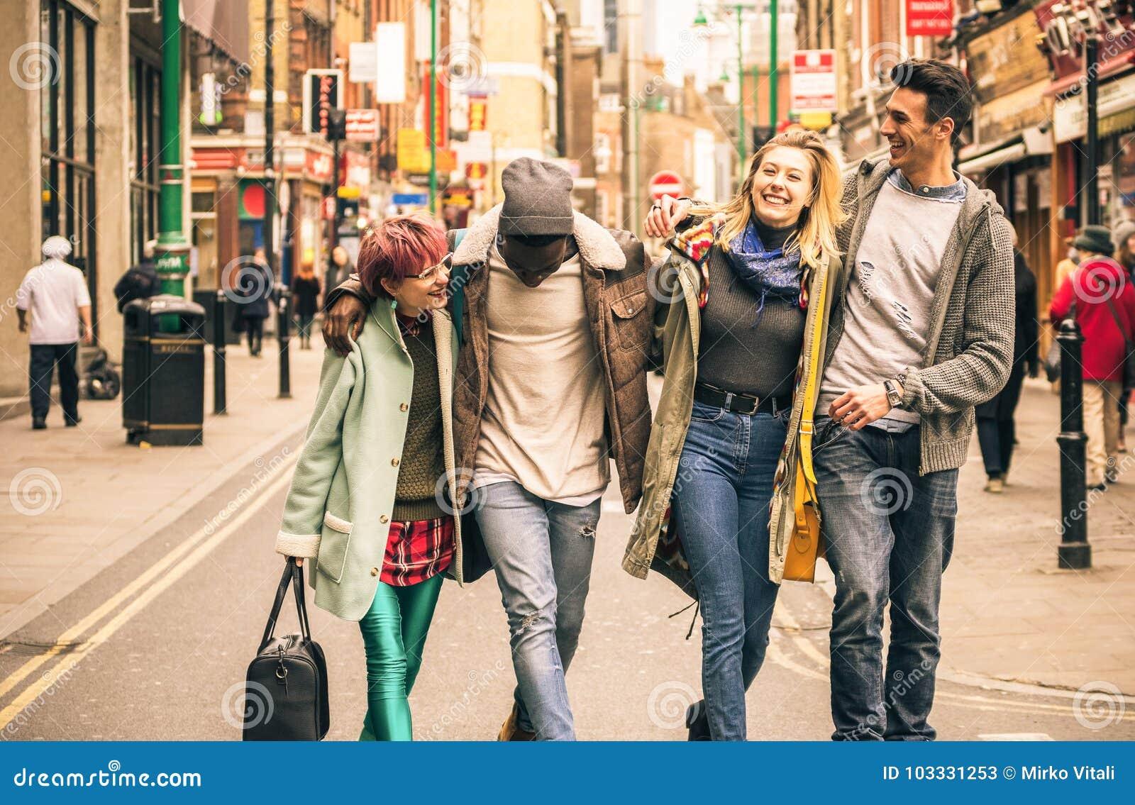 Amigos multirraciales felices que caminan en carril del ladrillo en Shoreditch Londres