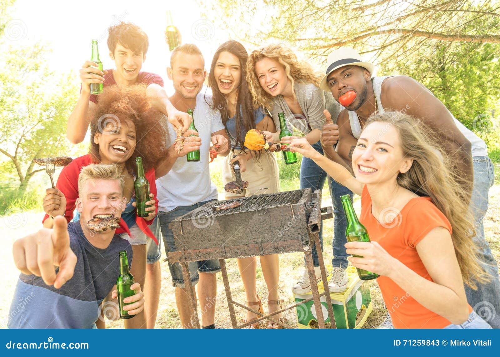 Amigos multirraciales felices que se divierten en la fiesta de jardín de la barbacoa