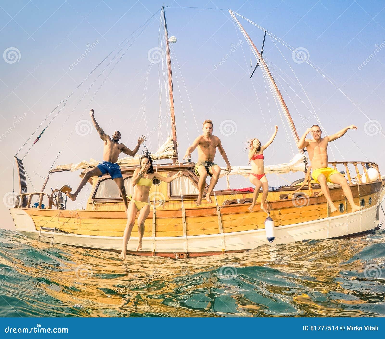 Amigos multirraciales jovenes que saltan del velero de madera