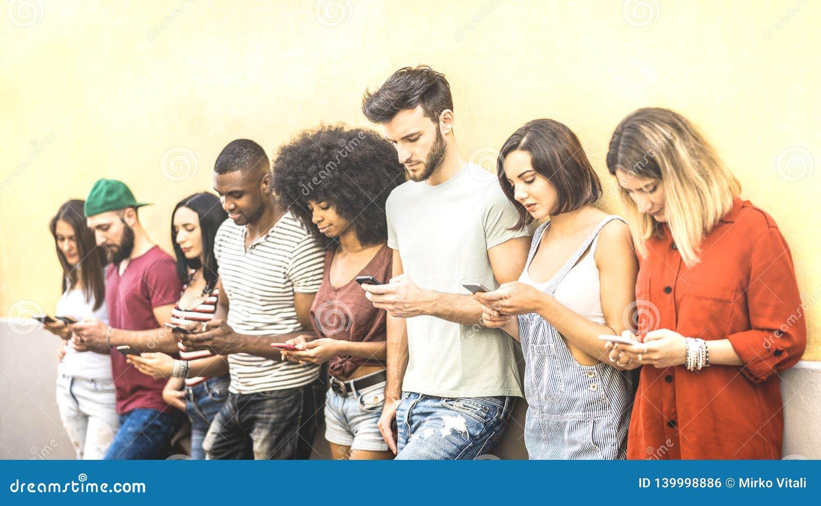 Amigos multirraciales que usan smartphone móvil en el coampus de la universidad - gente de Millenial enviciada por los teléfonos