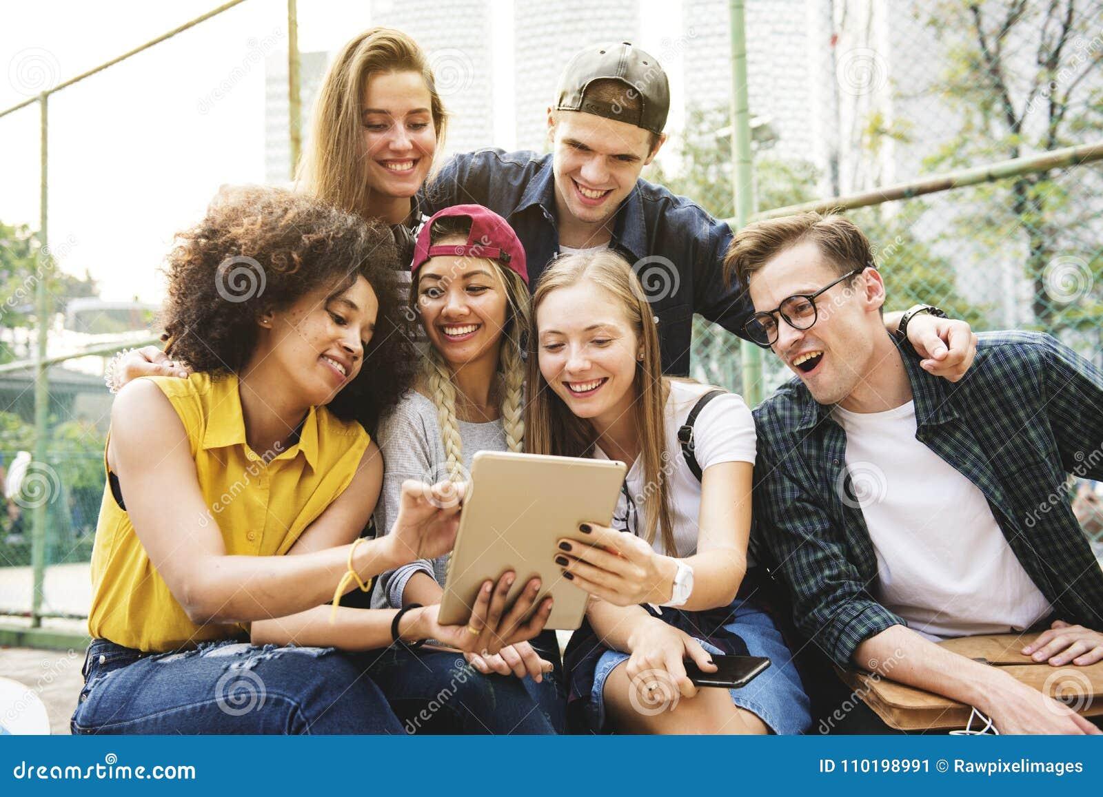 Amigos no parque usando uma tabuleta digital milenar e a juventude