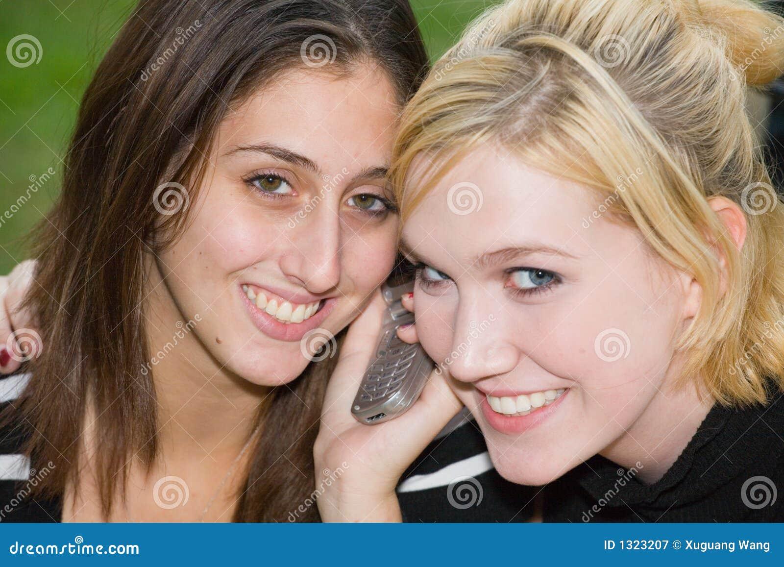 Amigos no telefone de pilha junto (Blonde novo bonito e Brune