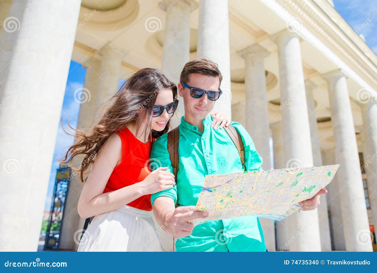 Amigos novos do turista que viajam em feriados no sorriso de Europa feliz Família caucasiano com o mapa da cidade à procura de