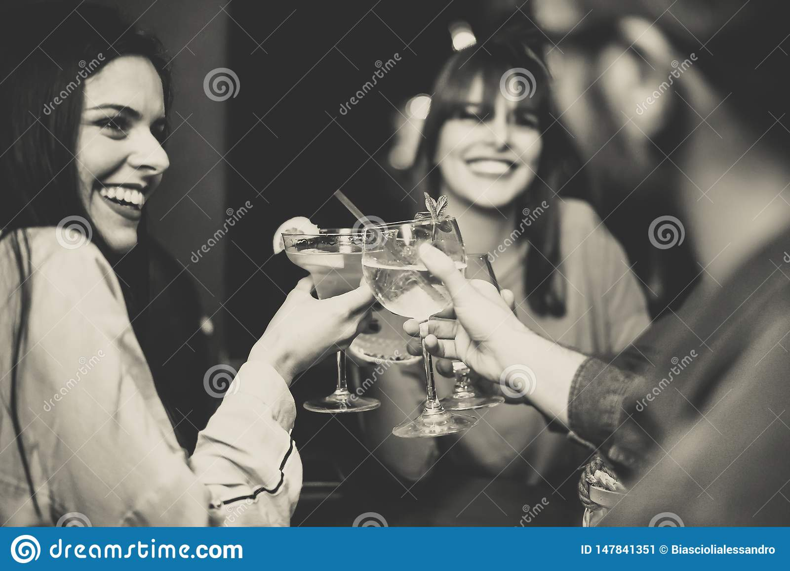 Amigos novos felizes que brindam e que cheering cocktail na barra do disco - pessoa multirracial que tem o divertimento que aprec
