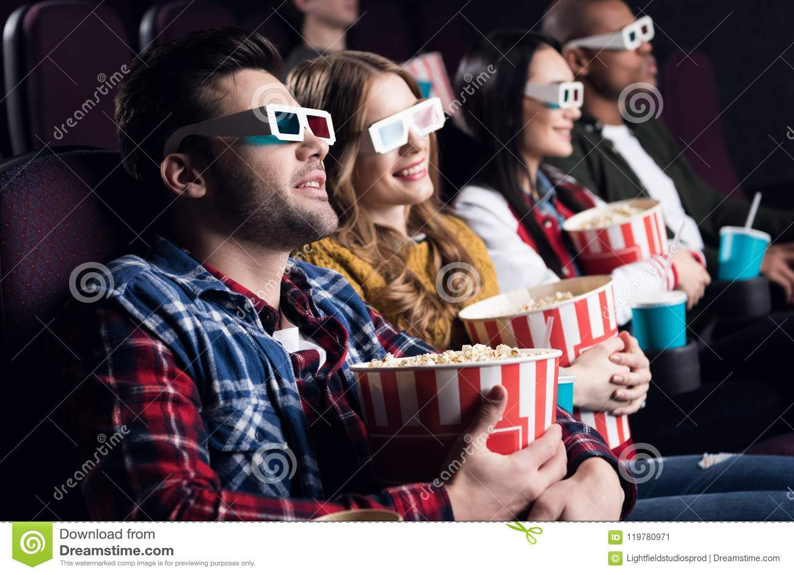 Amigos novos nos vidros 3d com pipoca e filme de observação da soda