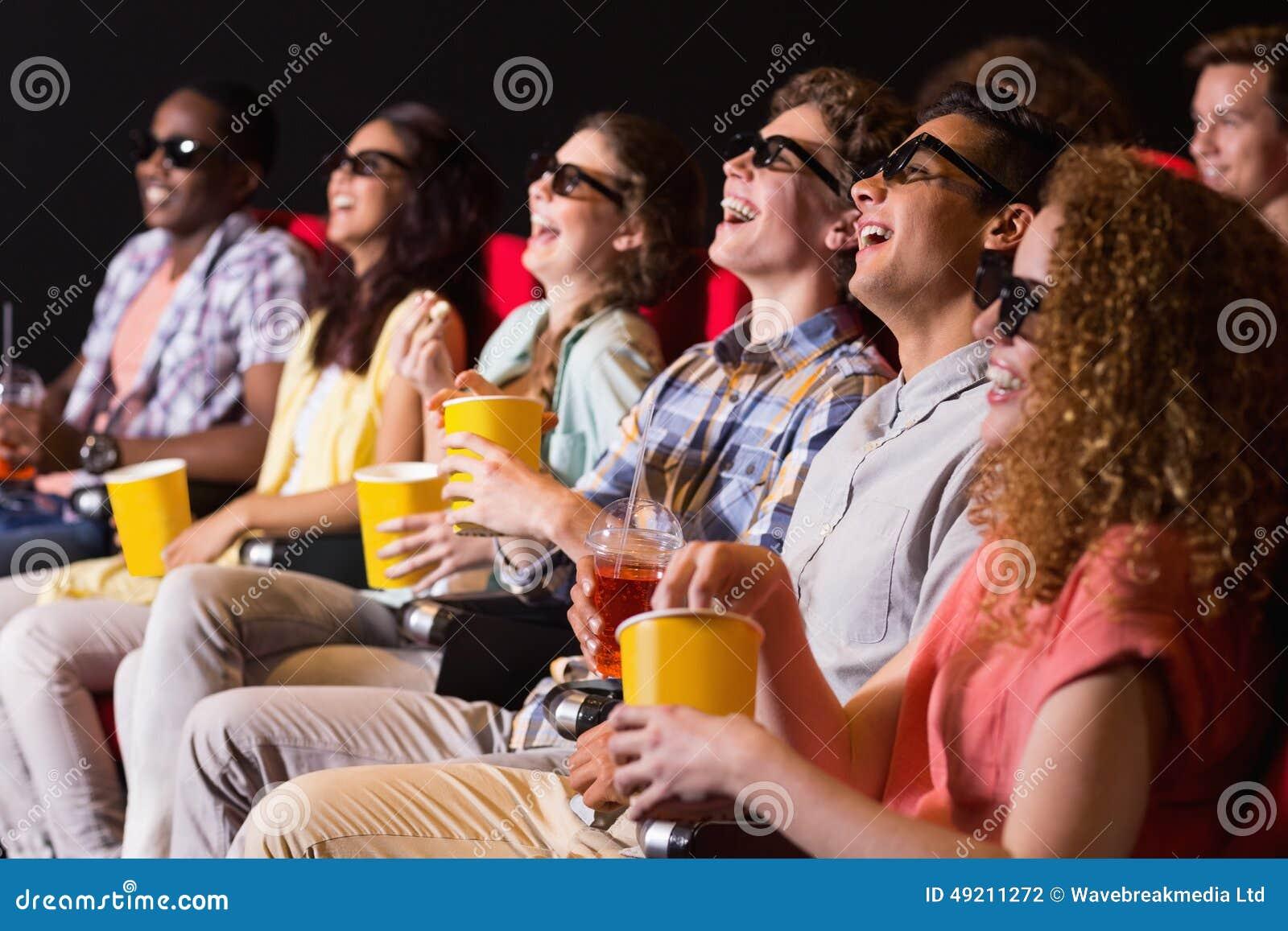 Amigos novos que olham um filme 3d