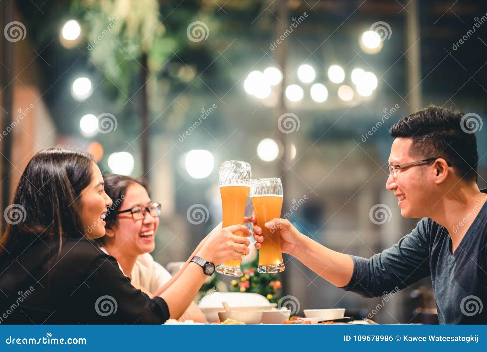 Amigos o compañeros de trabajo asiáticos que animan con la cerveza, celebrando junto en el restaurante o el club de noche Gente j