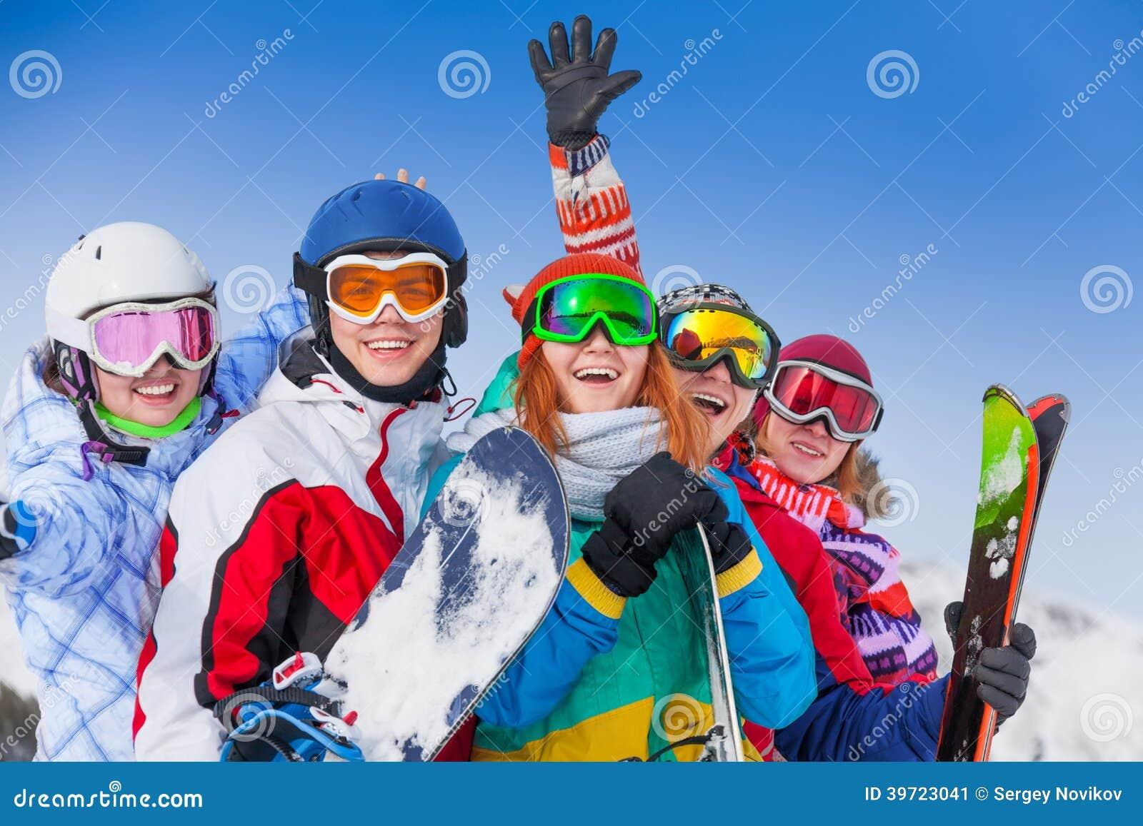 Amigos positivos com snowboards e esquis