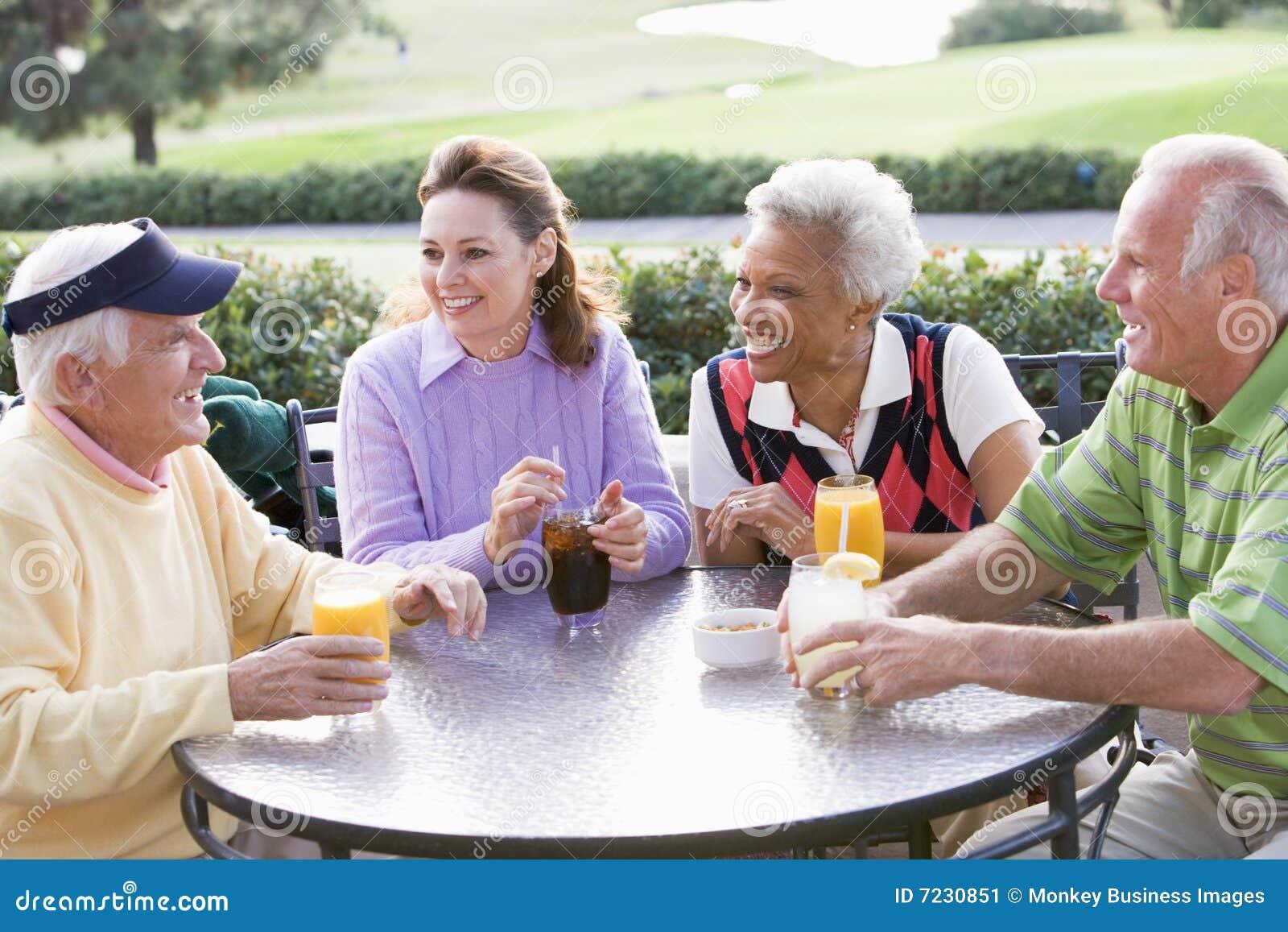 Amigos que apreciam uma bebida por um campo de golfe