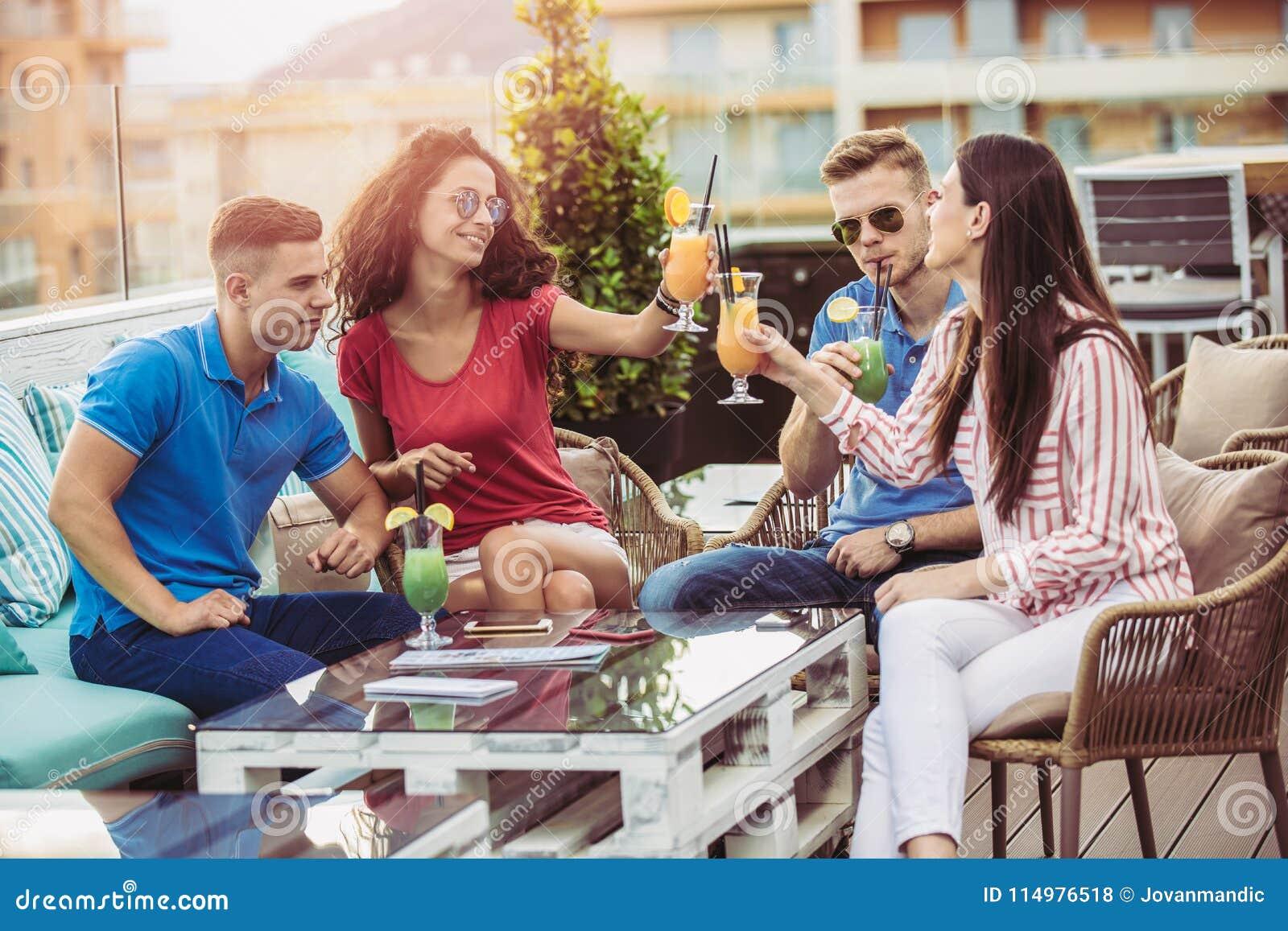 Amigos que bebem os cocktail exteriores em um balcão da sótão de luxo