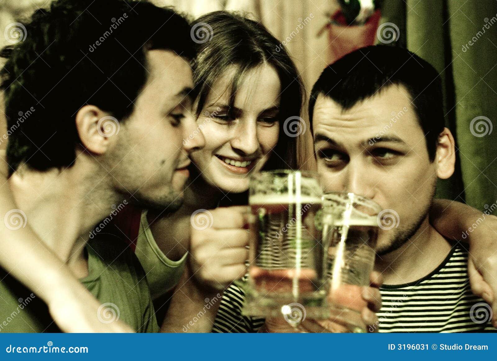 Amigos que beben la cerveza