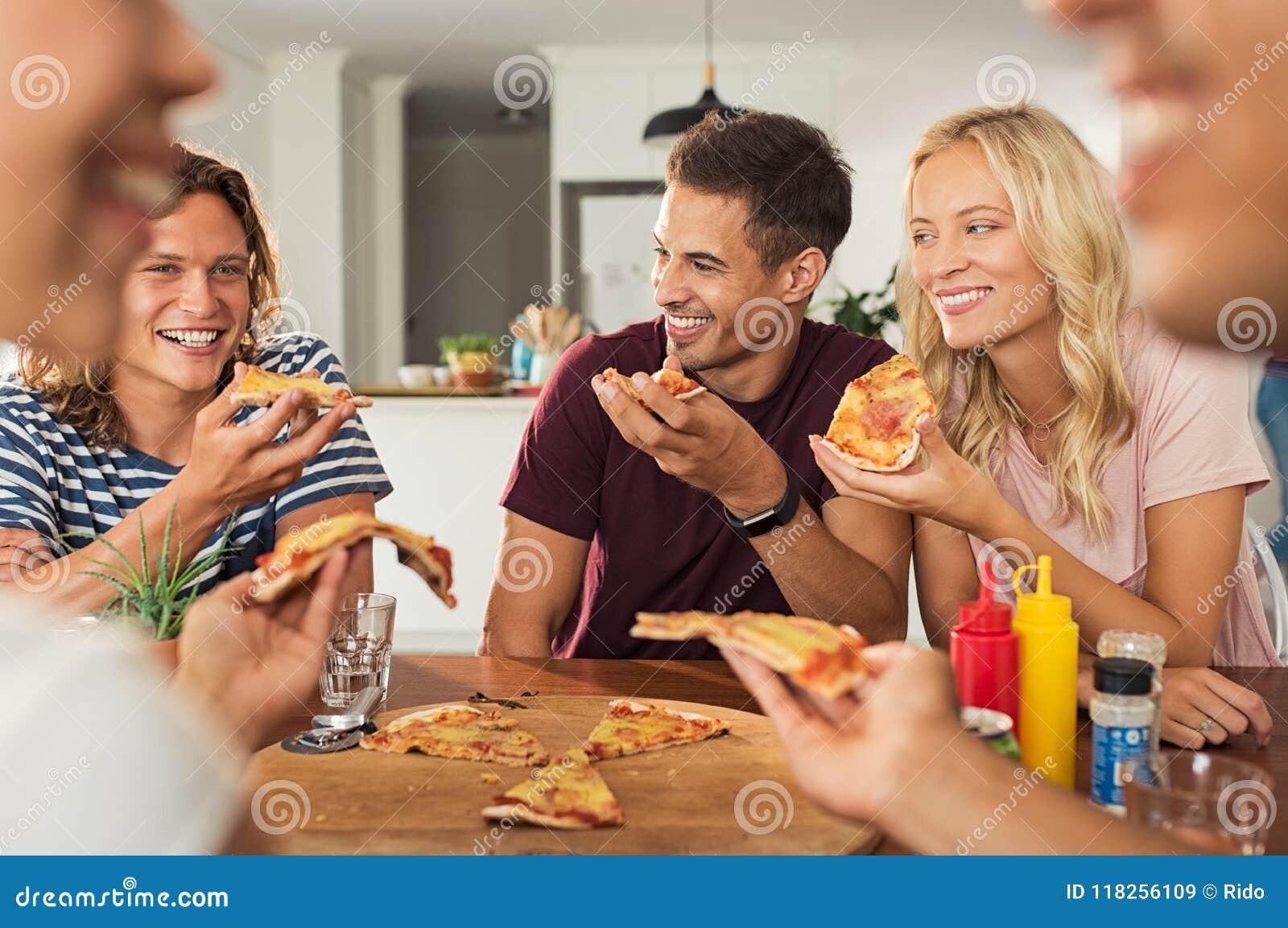 Amigos que comem a pizza em casa