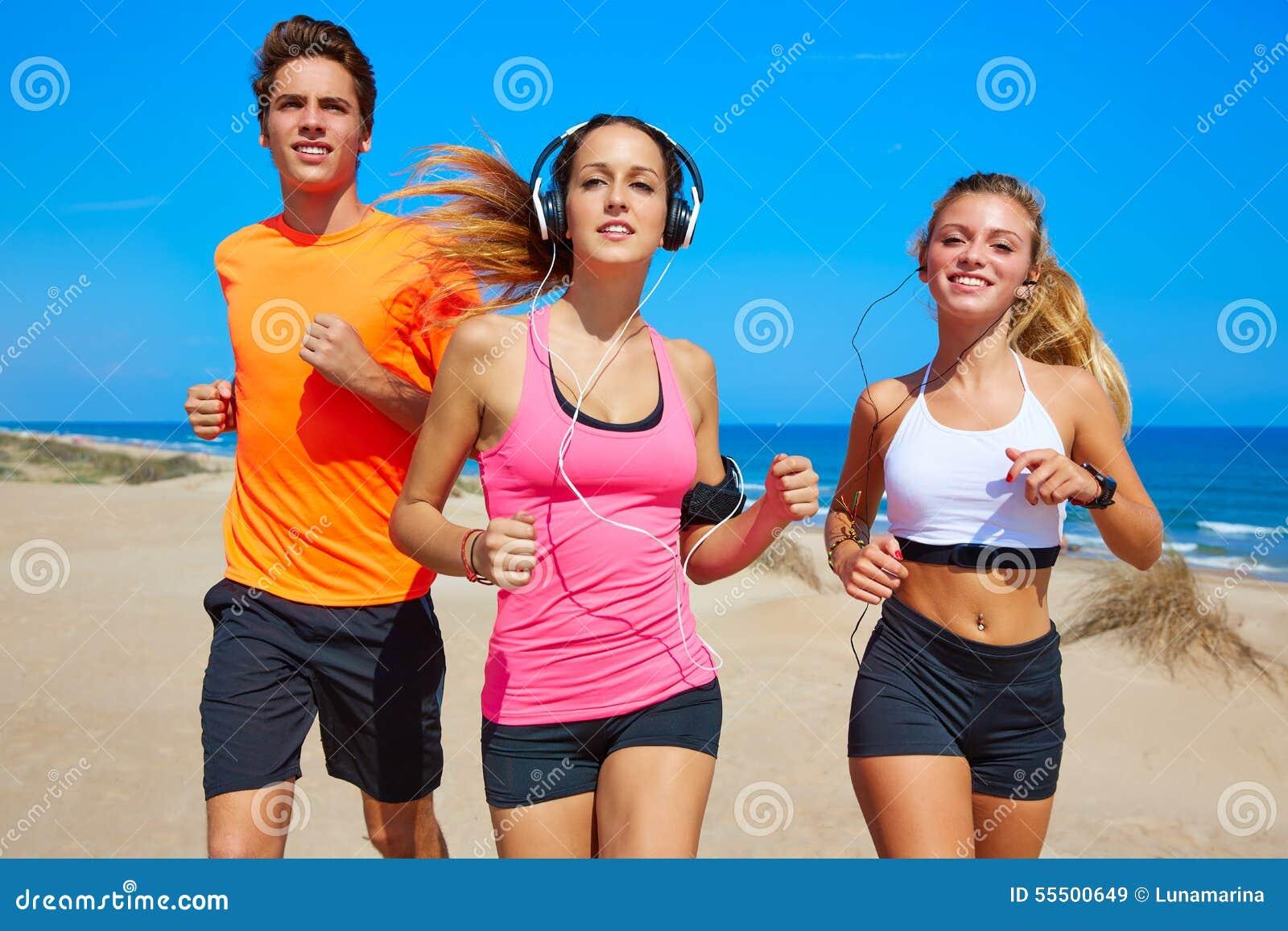 Amigos que correm na praia feliz no verão