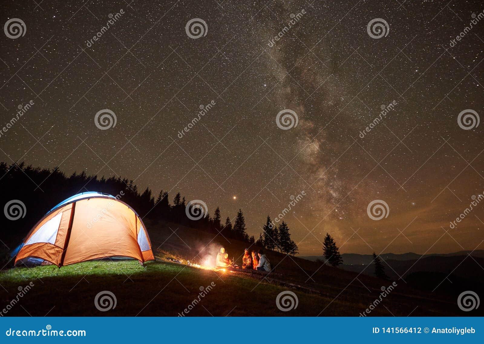Amigos que descansam ao lado do acampamento, fogueira sob o céu estrelado da noite