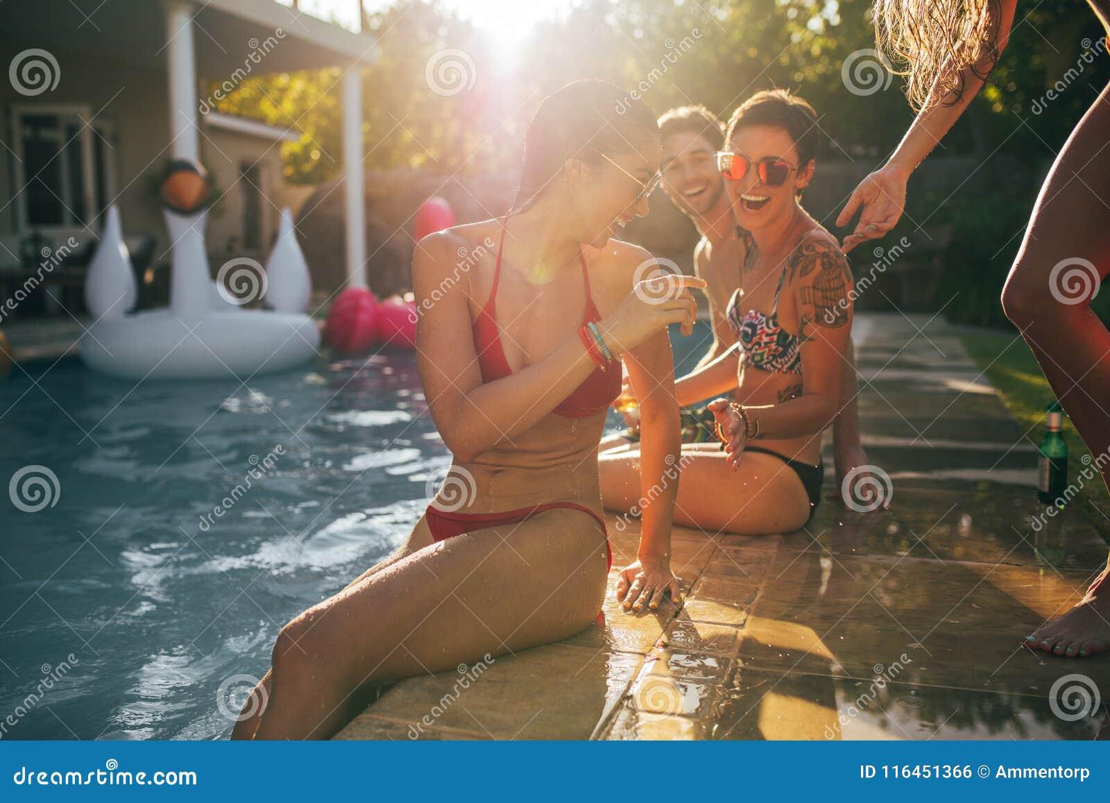 Amigos que gozan en la fiesta en la piscina en un día de verano