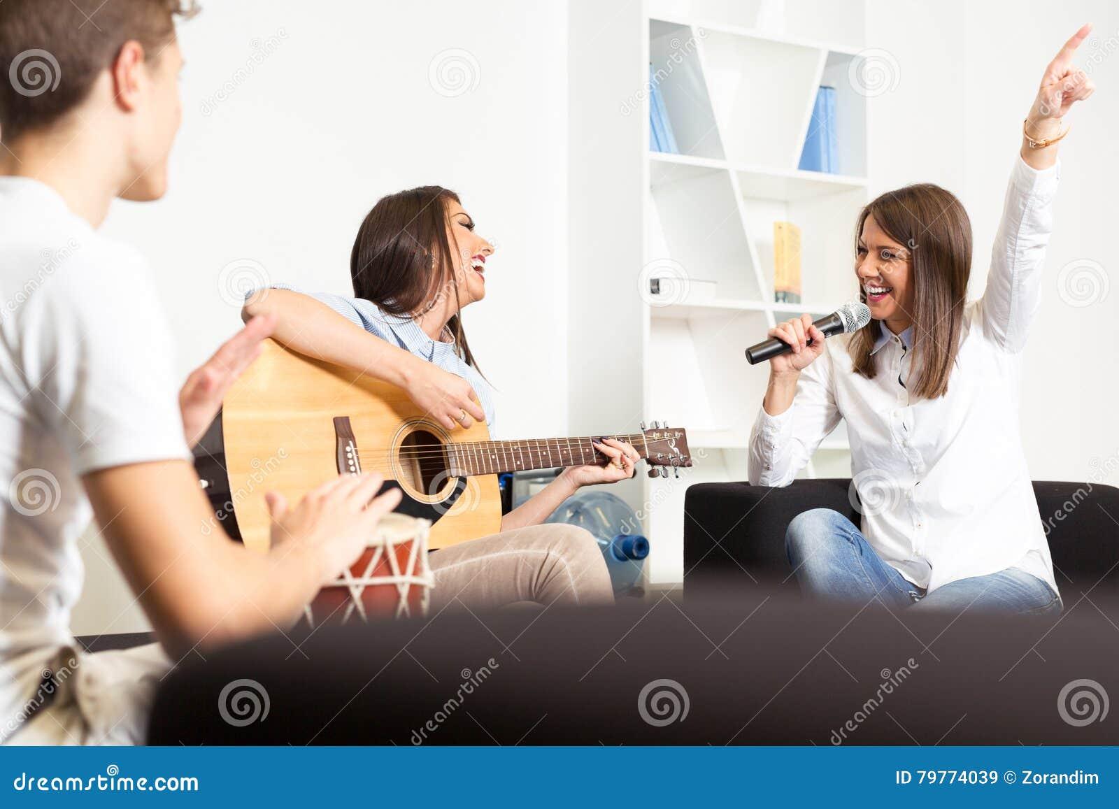 Amigos que gozan tocando la guitarra y cantando junto