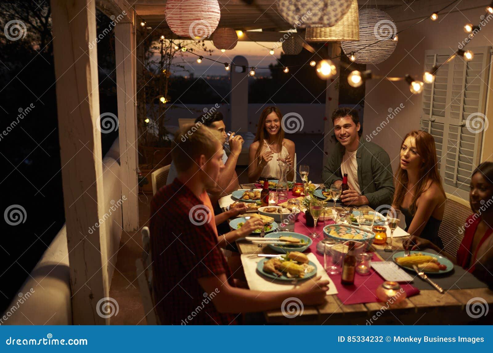 Amigos que hablan en un partido de cena en un patio, Ibiza, España