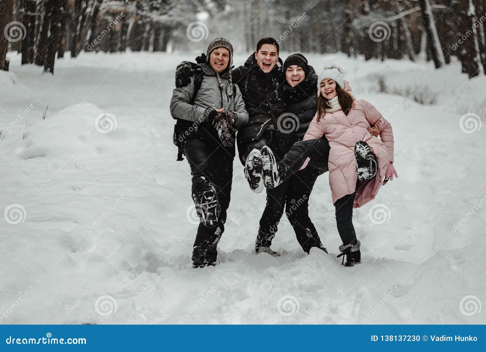 Amigos que jogam com neve no parque
