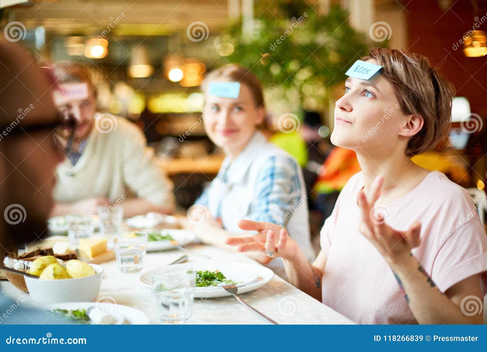 Amigos que juegan al juego en restaurante