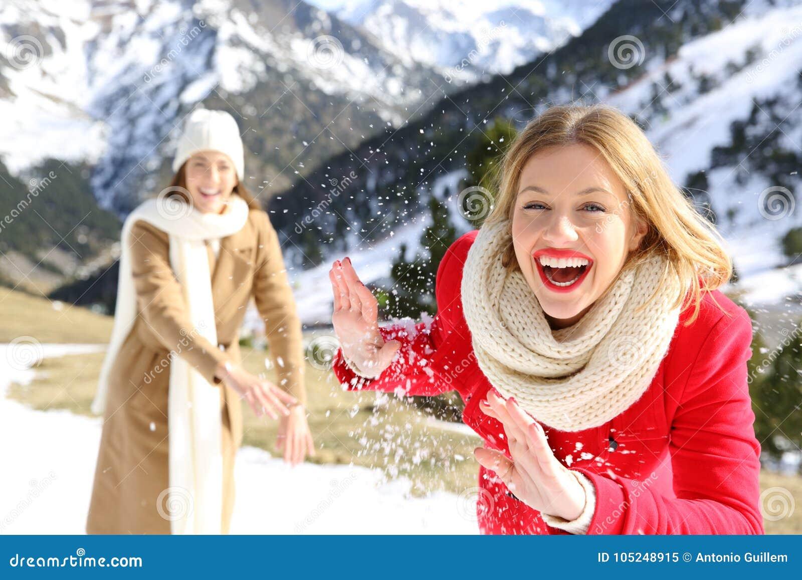 Amigos que lanzan bolas de nieve en una montaña nevosa en invierno