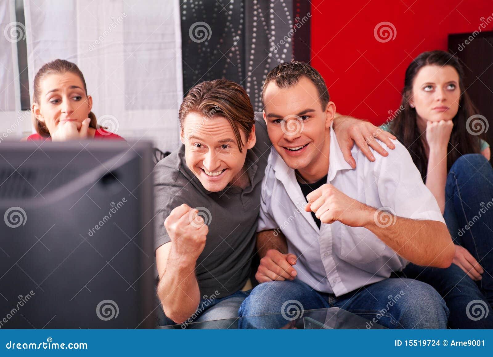 Amigos que miran el juego emocionante en la TV