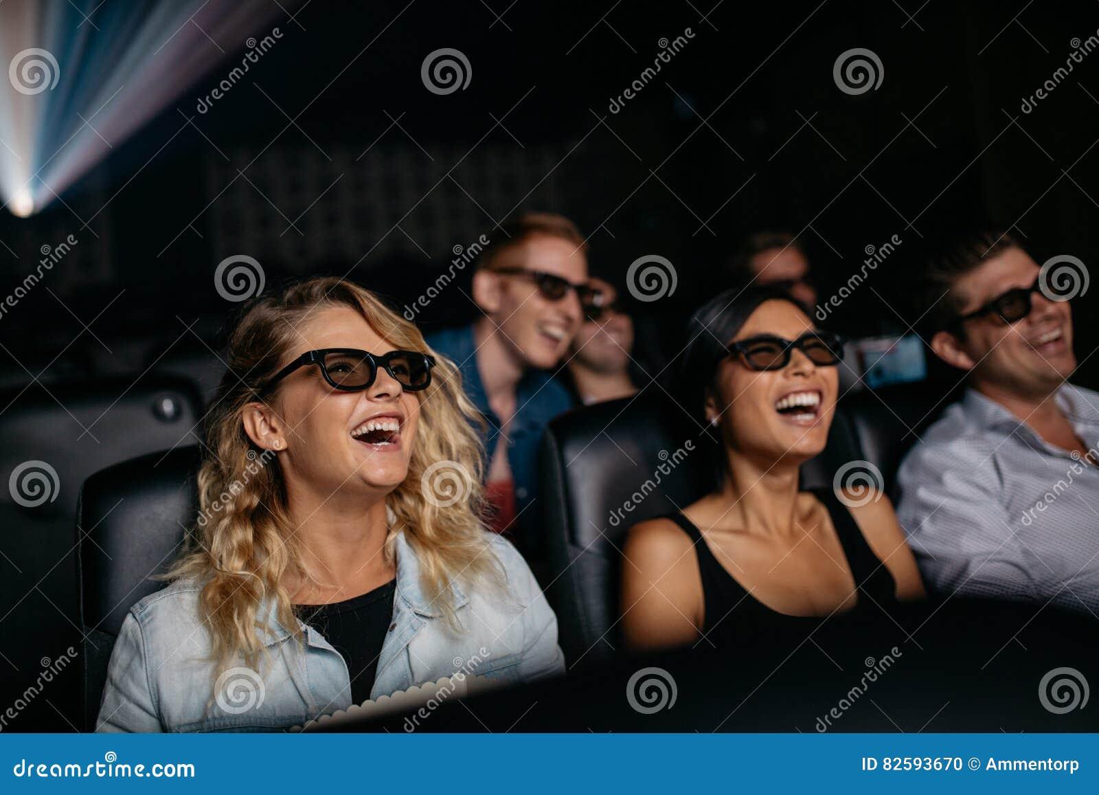 Amigos que miran la película 3d y la risa