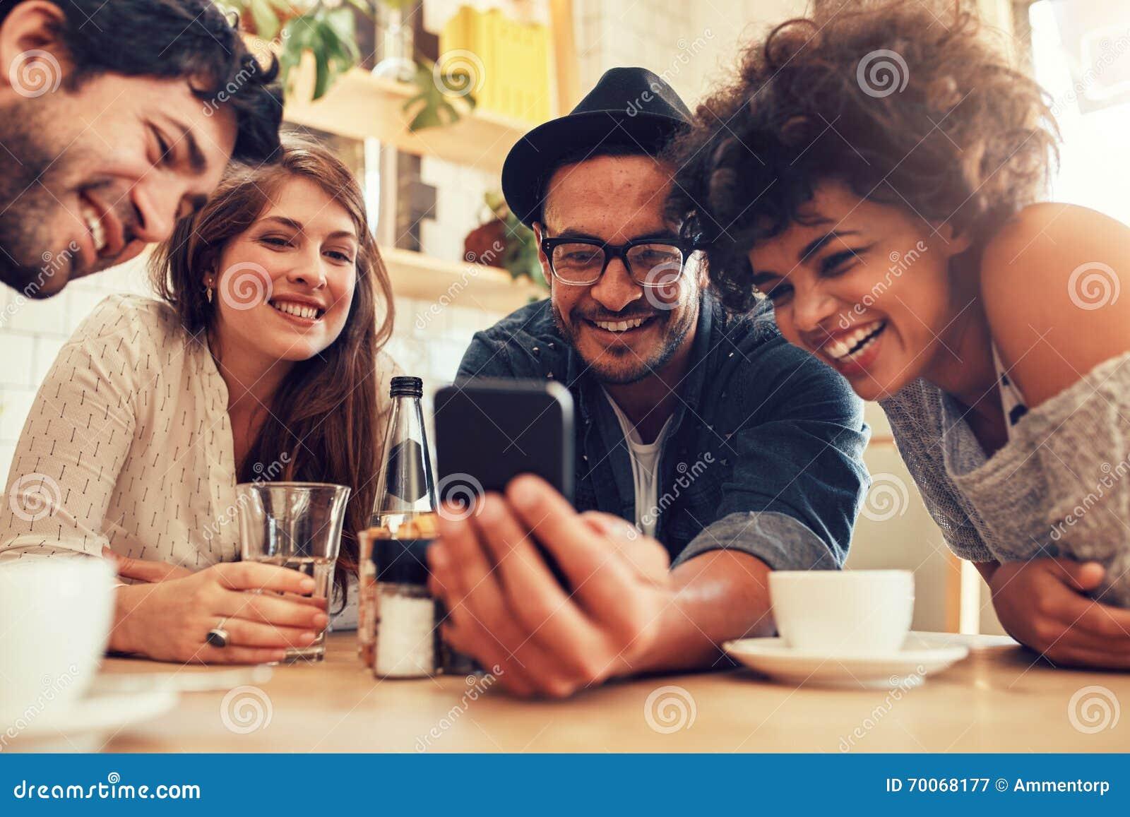 Amigos que miran las fotos en el teléfono móvil
