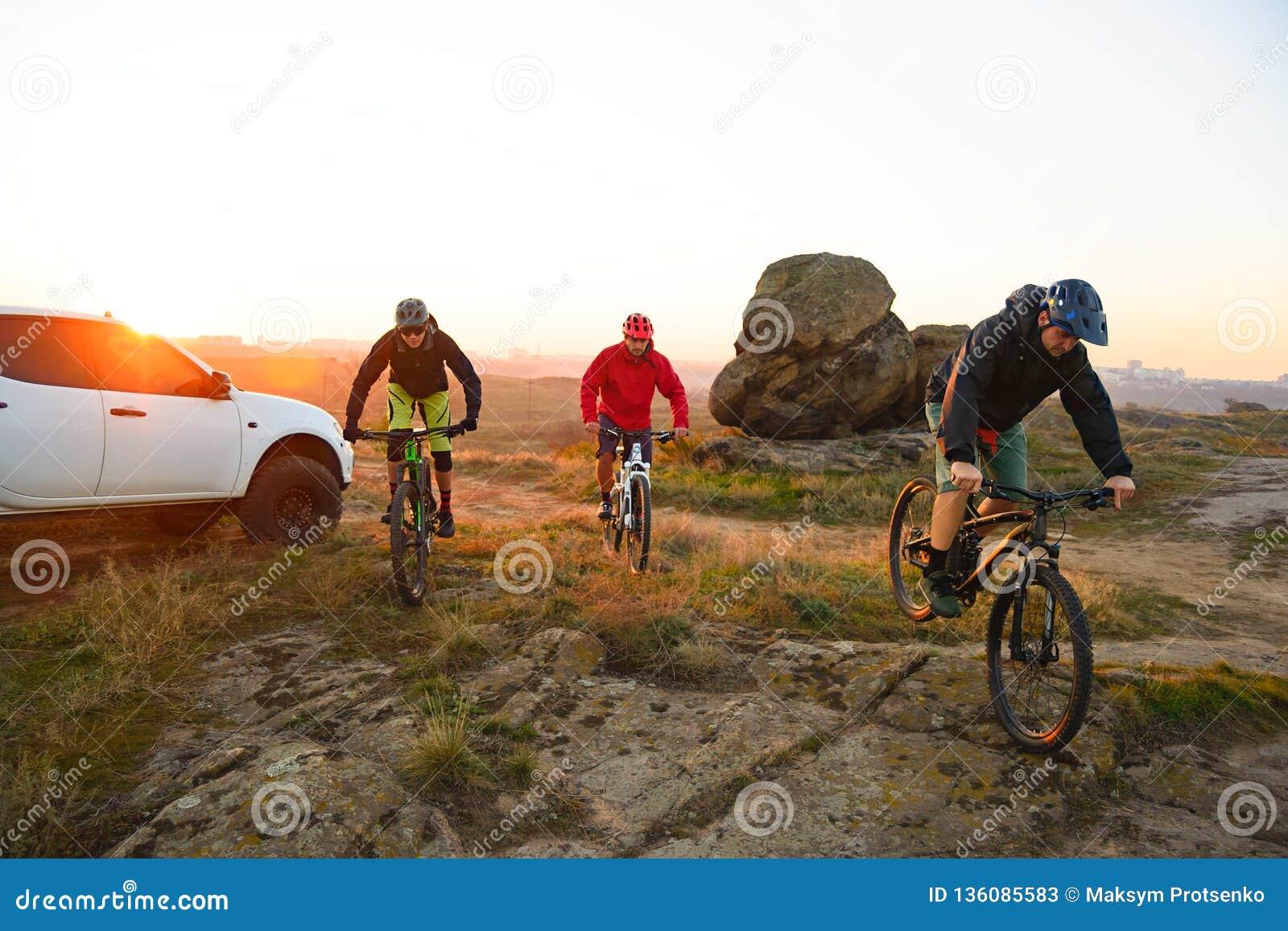 Amigos que montam bicicletas nas montanhas na frente do caminhão de Off Road do recolhimento no por do sol Conceito da aventura e