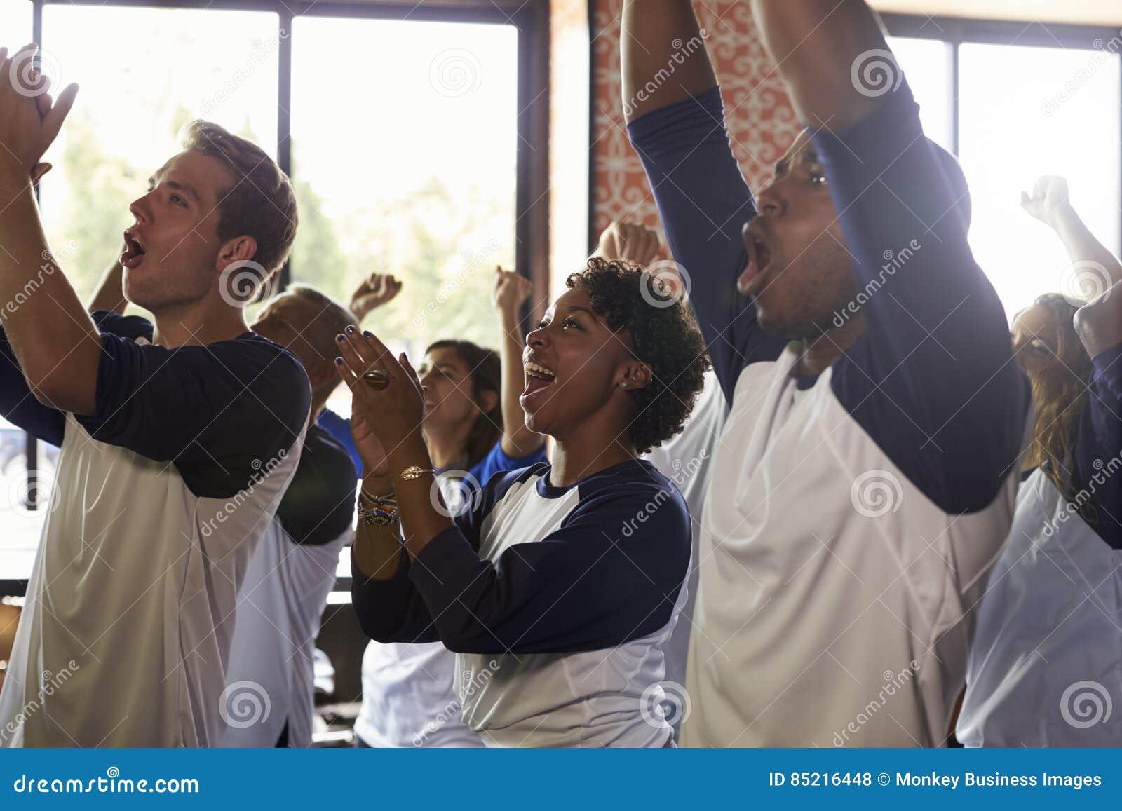 Amigos que olham o jogo na comemoração da barra de esportes