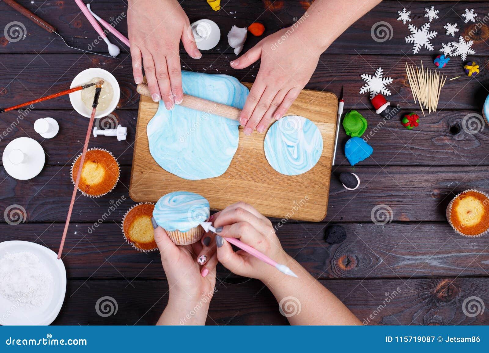 Amigos que rolam a mástique dos confeitos e que decoram os queques, vi
