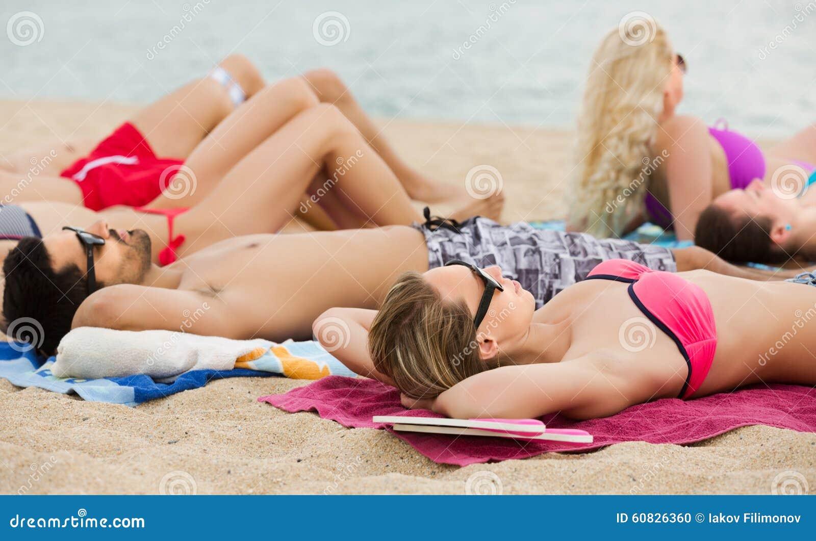 Amigos que se relajan en la playa arenosa