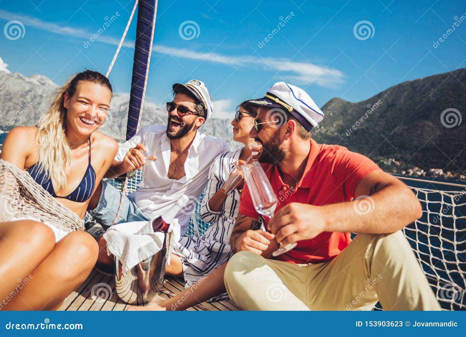 Amigos que sentam-se na plataforma do veleiro e que têm o divertimento F?rias, curso, mar, amizade e conceito dos povos