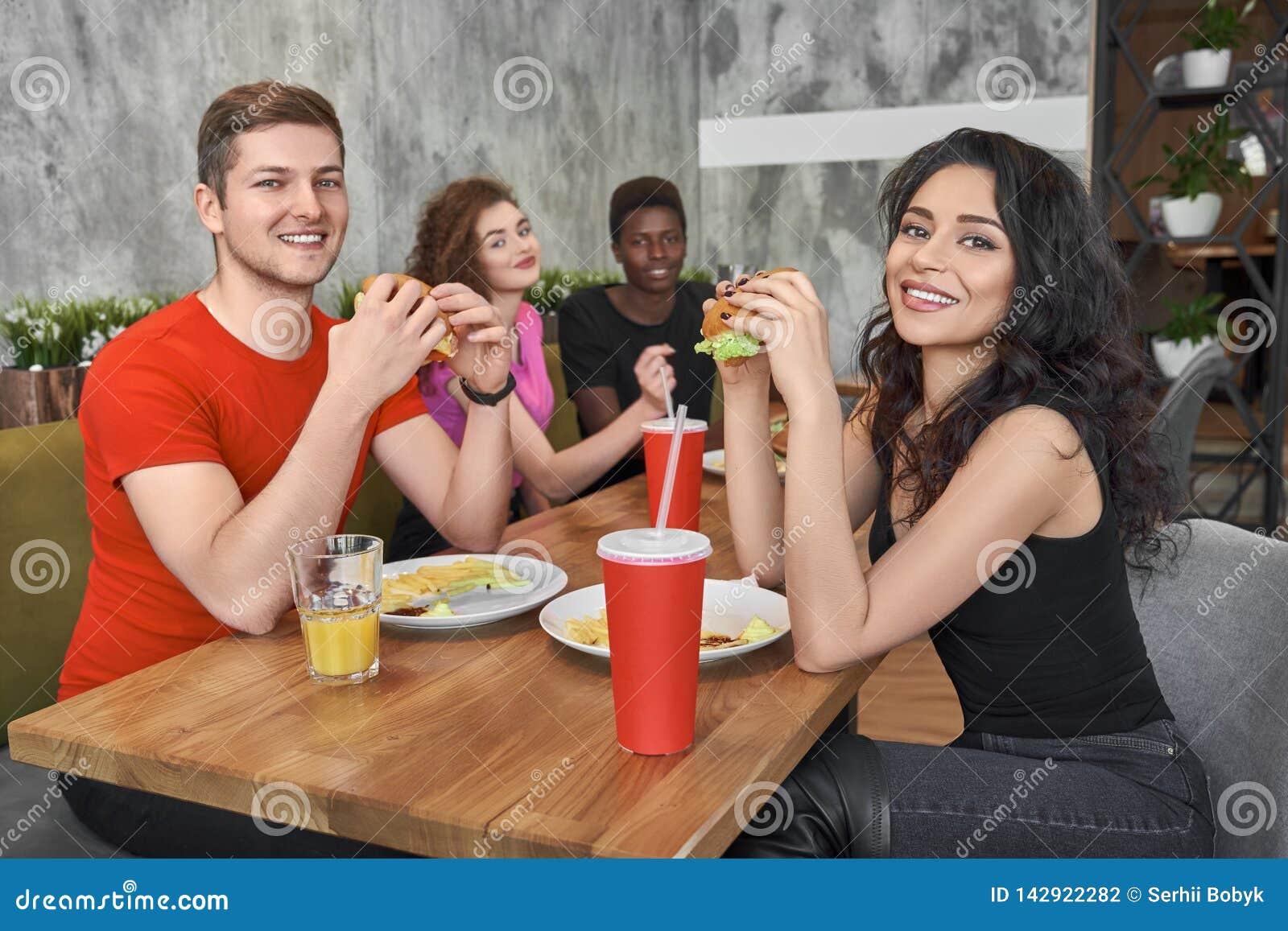 Amigos que sentam-se no café do fast food, comendo Hamburger