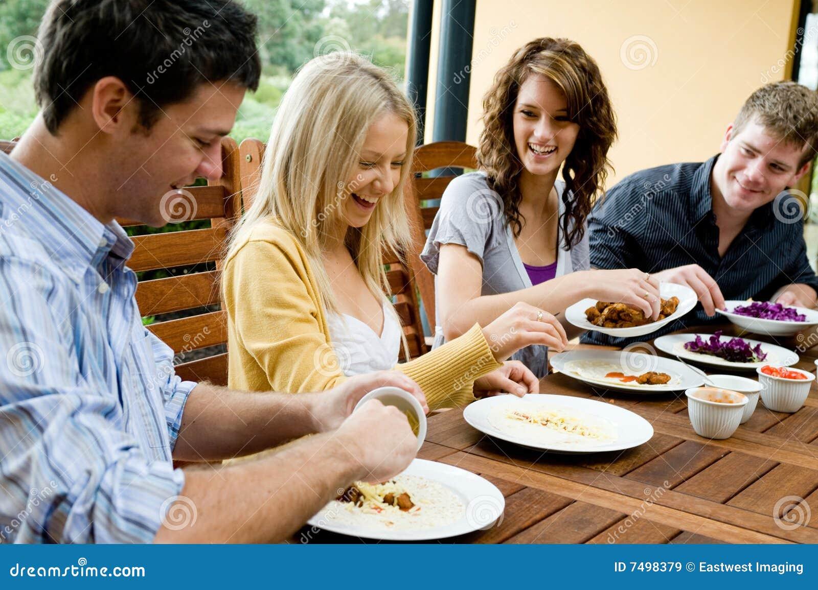Amigos que têm o jantar