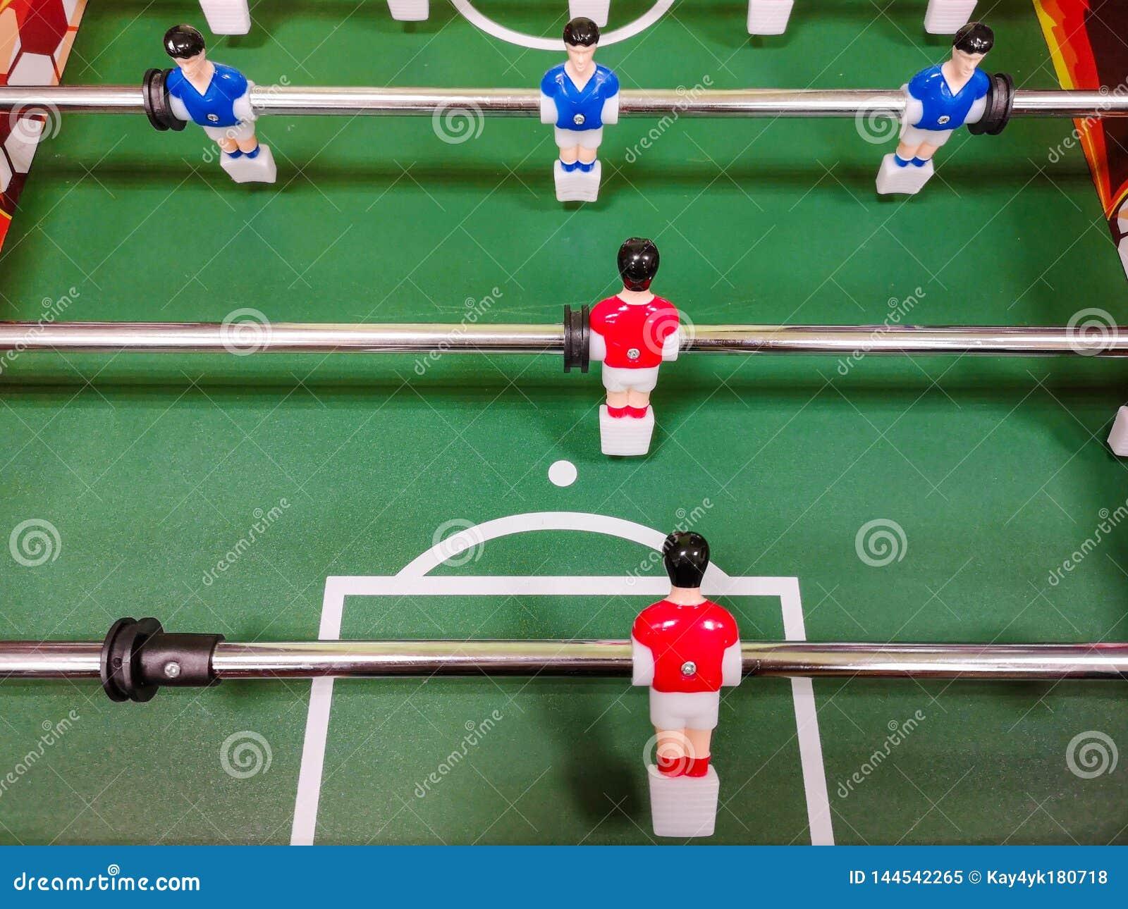Amigos que t?m o divertimento que joga junto o foosball Colegas que jogam o futebol da tabela na ruptura Povos do escrit?rio que