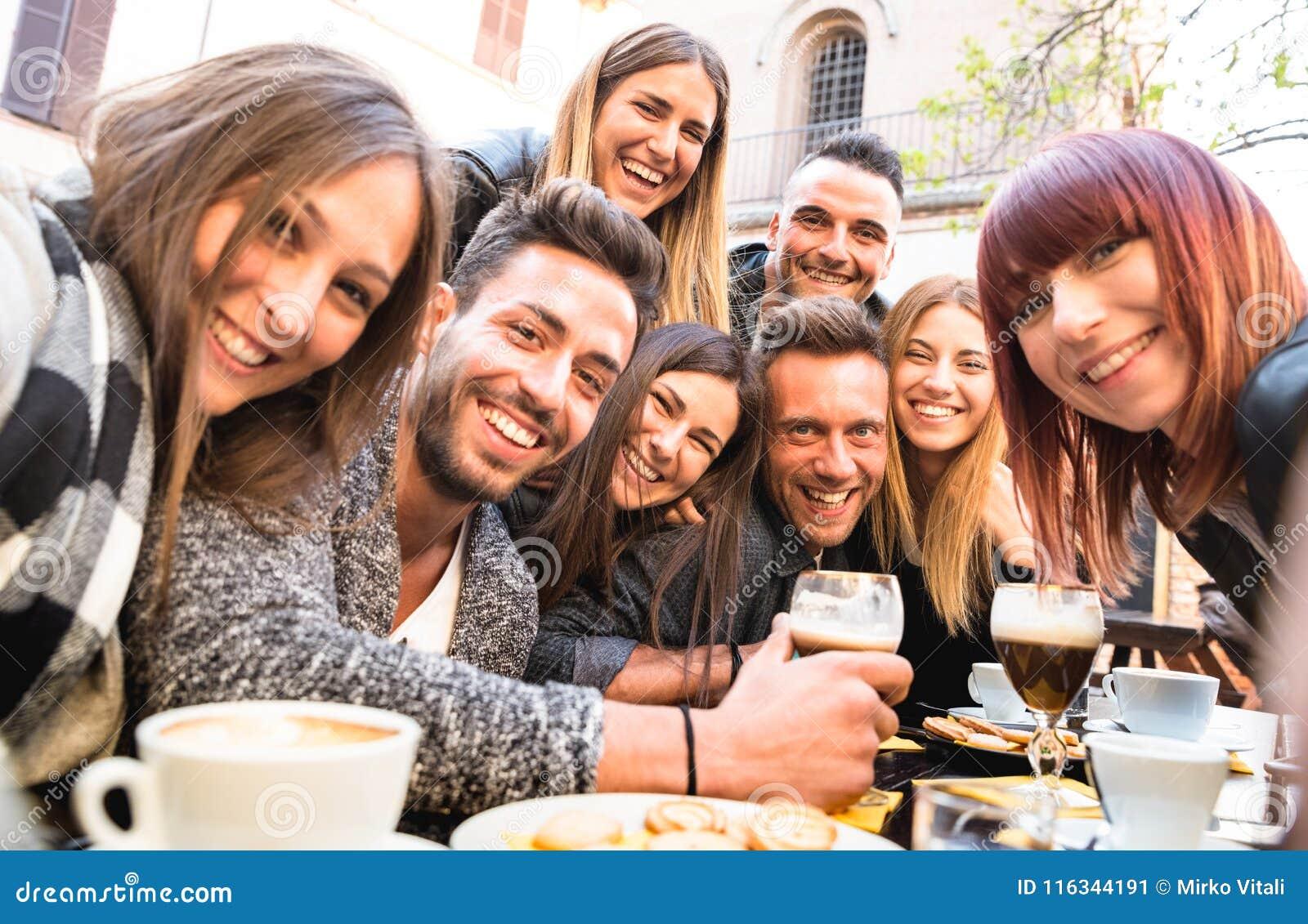 Amigos que tomam o selfie no cappuccino bebendo do restaurante da barra e