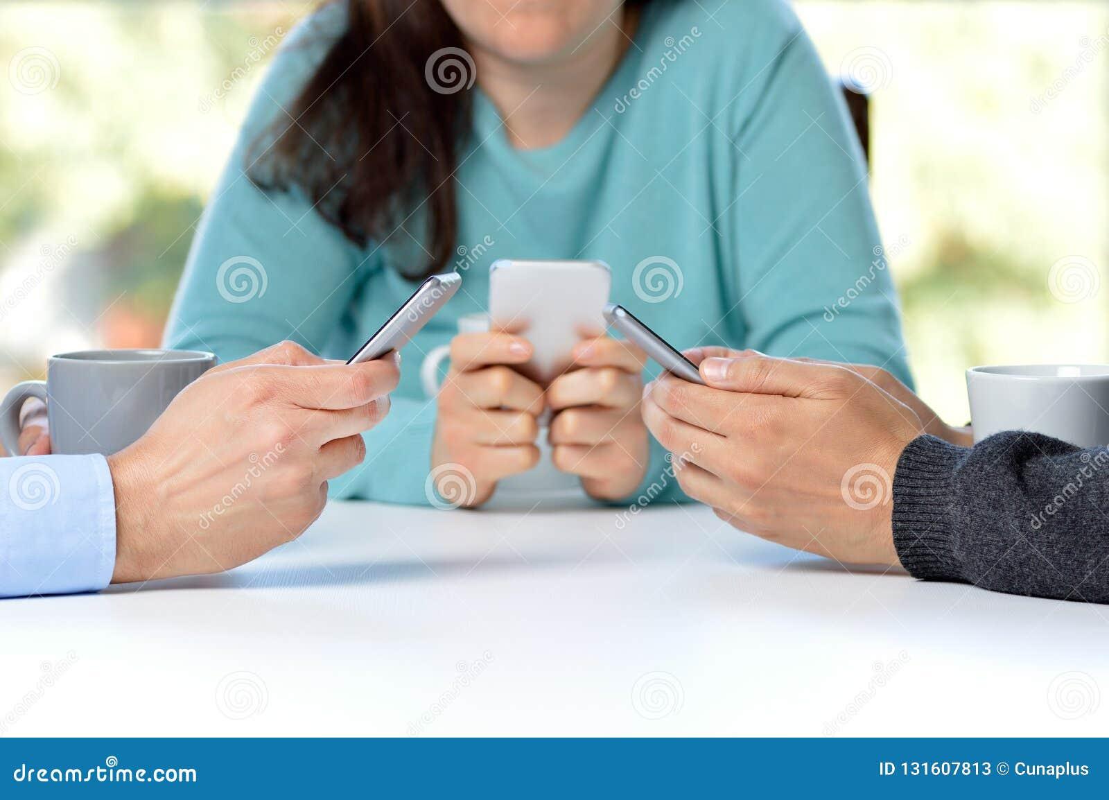 Amigos que usan sus smartphones en la barra