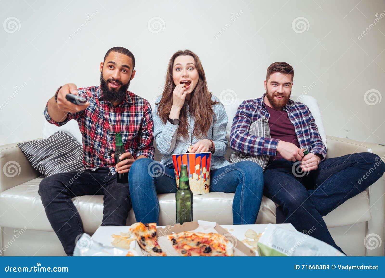 Amis étonnés heureux regardant la TV à la maison ensemble