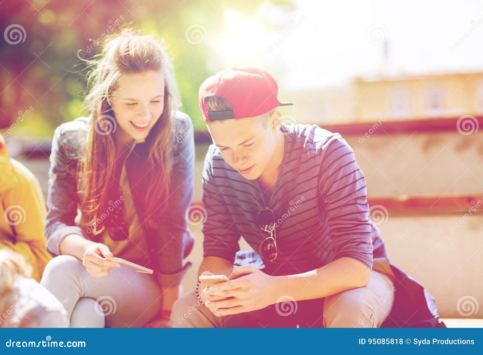 Amis adolescents heureux avec des smartphones dehors
