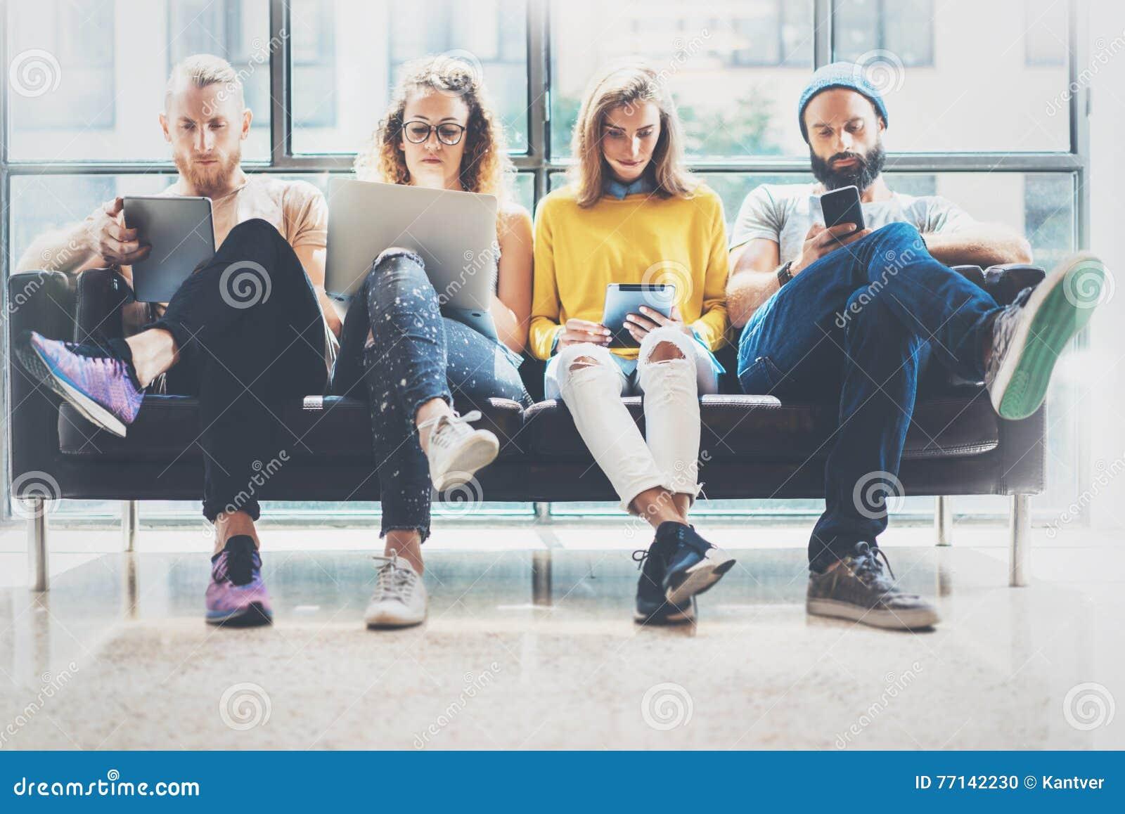 Amis adultes de hippies de groupe reposant Sofa Using Modern Gadgets Concept de travail d équipe d amitié de démarrage d entrepri