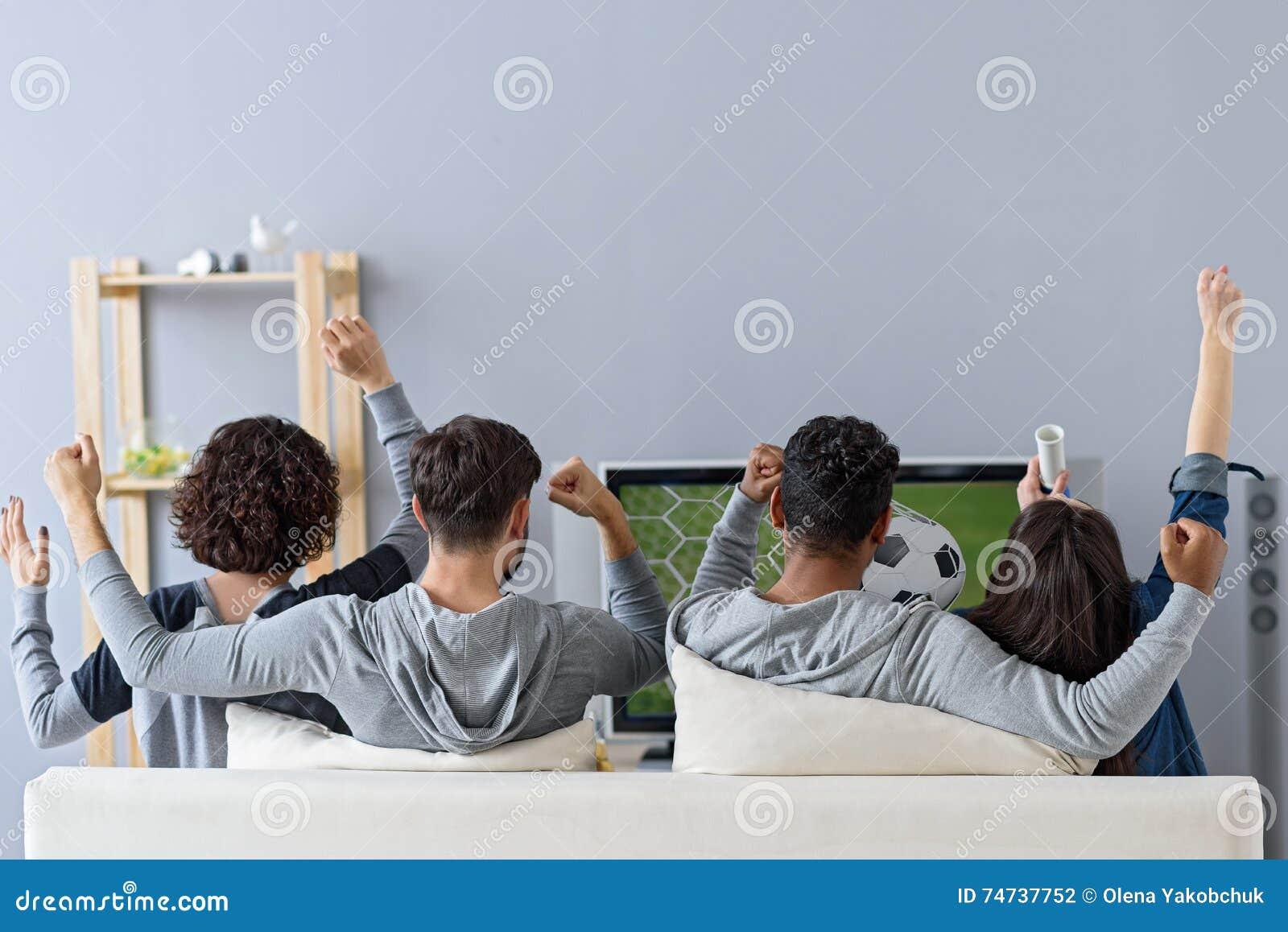 Amis appréciant le football dans la TV