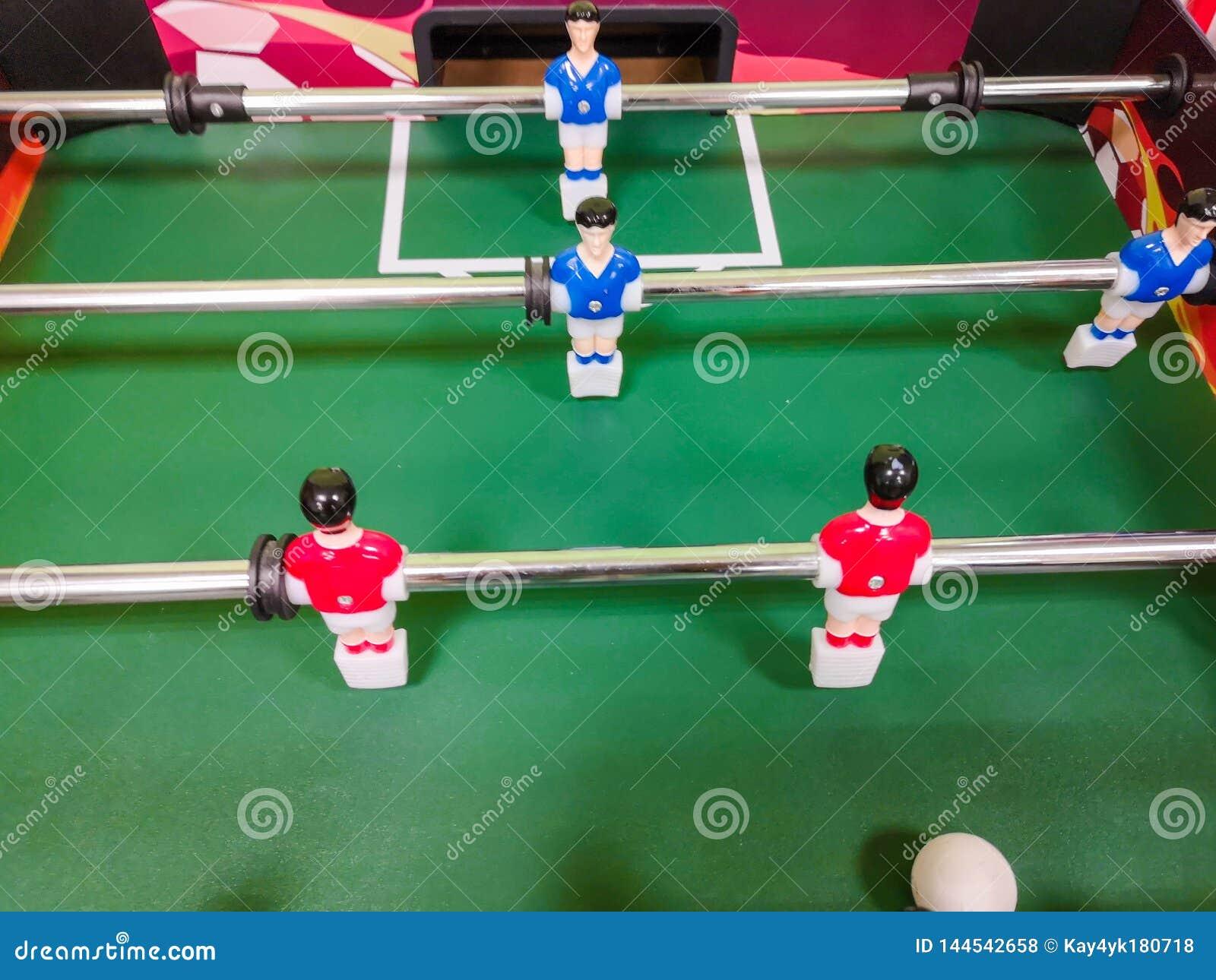 Amis ayant l amusement jouant ensemble le foosball Coll?gues jouant le football de table sur la coupure Personnes de bureau appr?