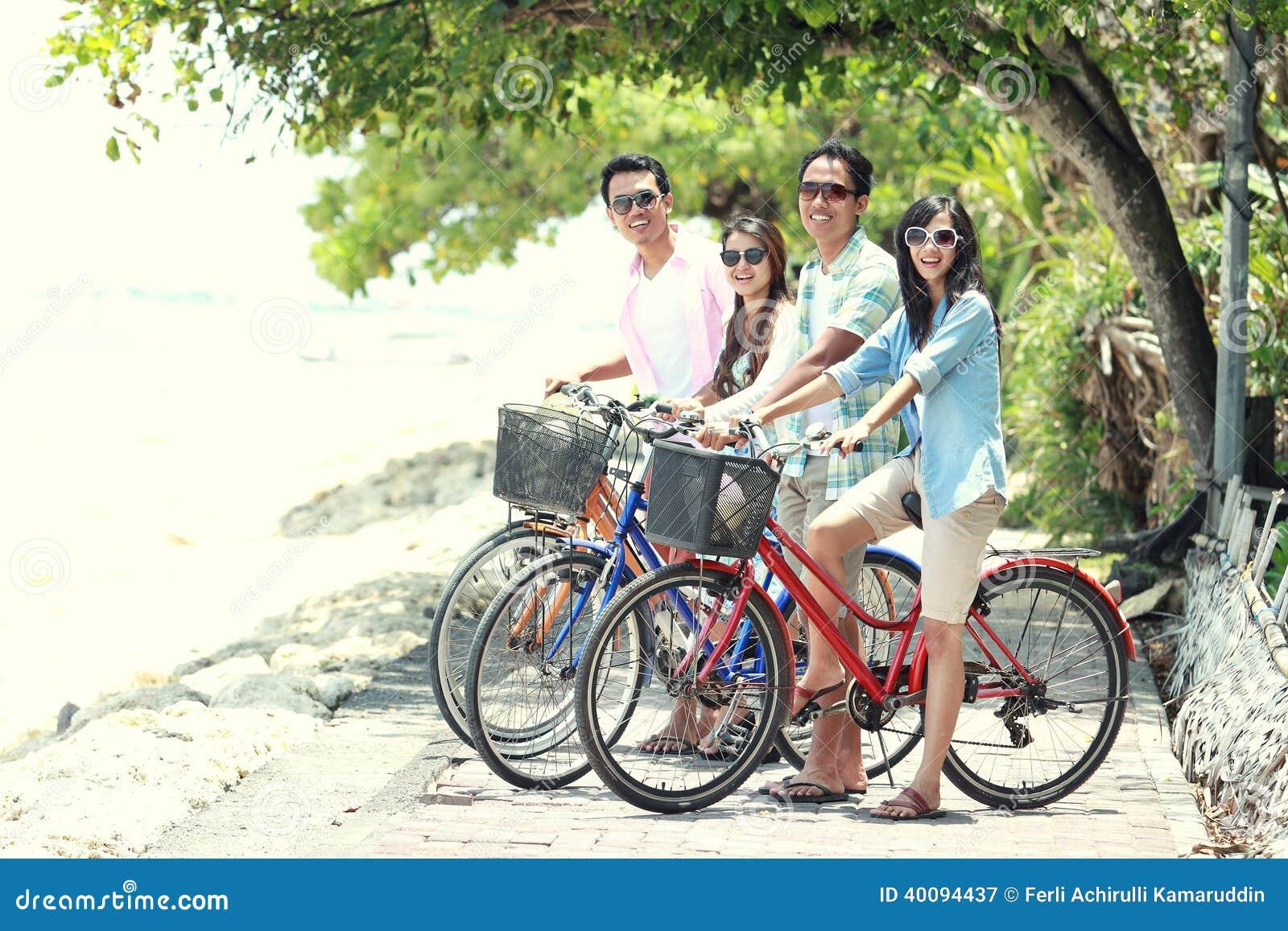 Amis ayant la bicyclette d équitation d amusement ensemble