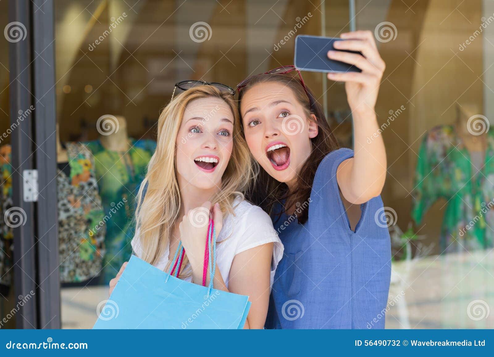 Amis de sourire heureux prenant un selfie
