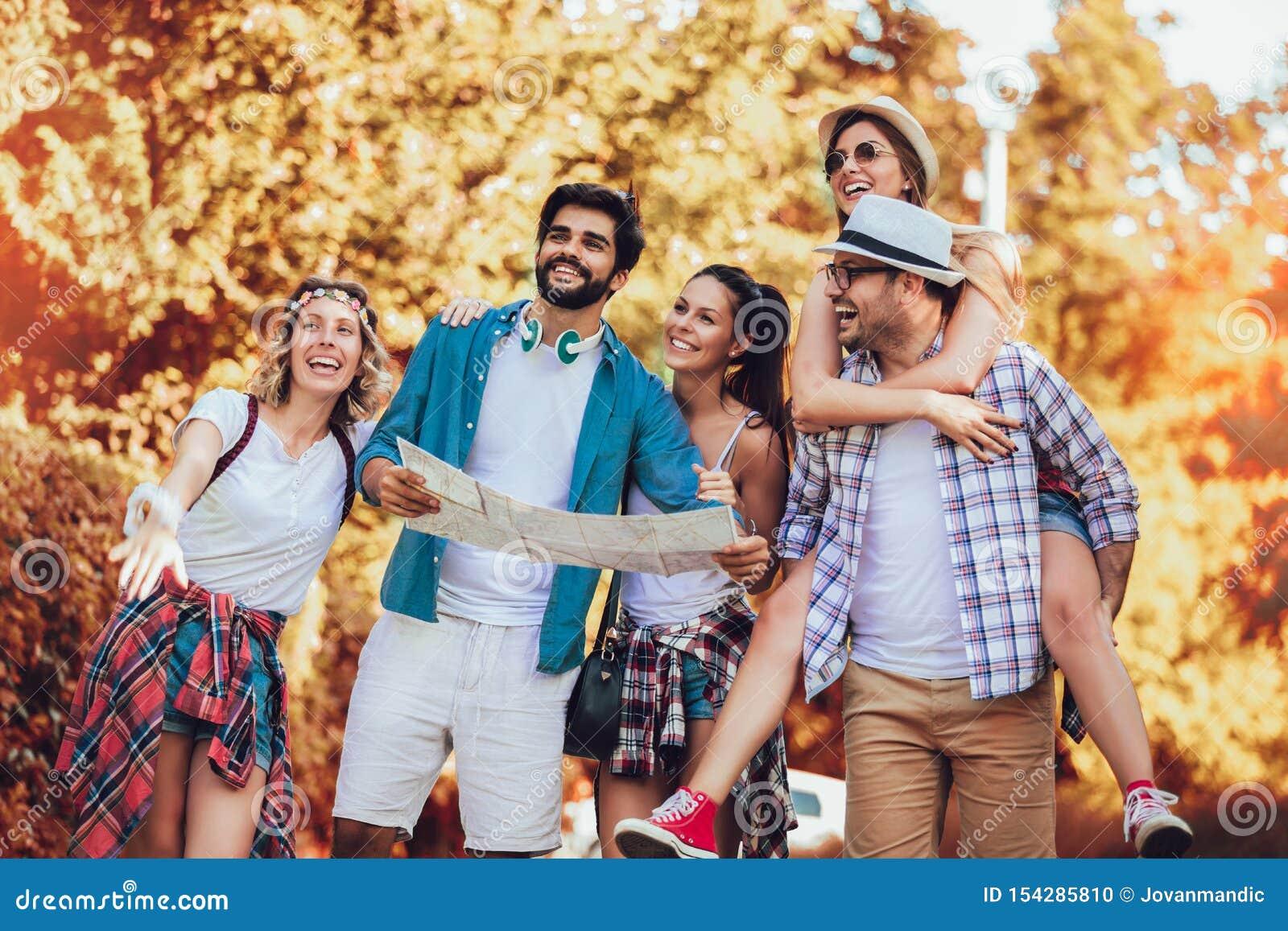 Amis de sourire marchant avec des sacs à dos en bois - aventure, voyage, tourisme, hausse et concept de personnes