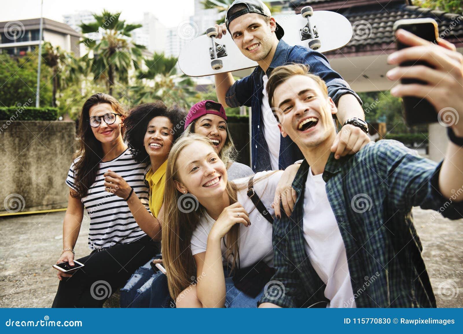 Amis en parc prenant un selfie de groupe millénaire et la jeunesse c